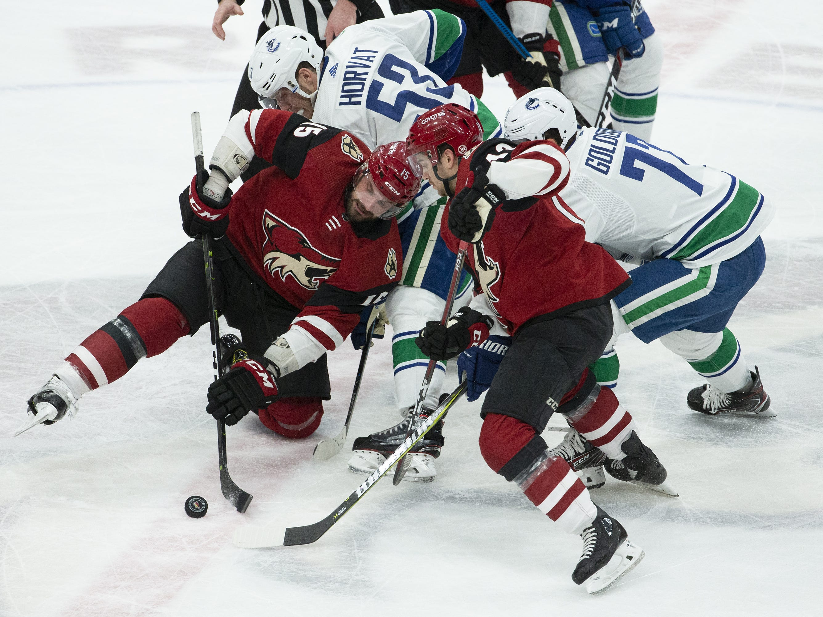 Arizona Coyotes center Brad Richardson (15) and Arizona center Vinnie Hinostroza (13) battle Vancouver Canucks center Bo Horvat (53) and right wing Nikolay Goldobin (77) for the puck during a NHL game at Gila River Arena in Glendale on February 28.