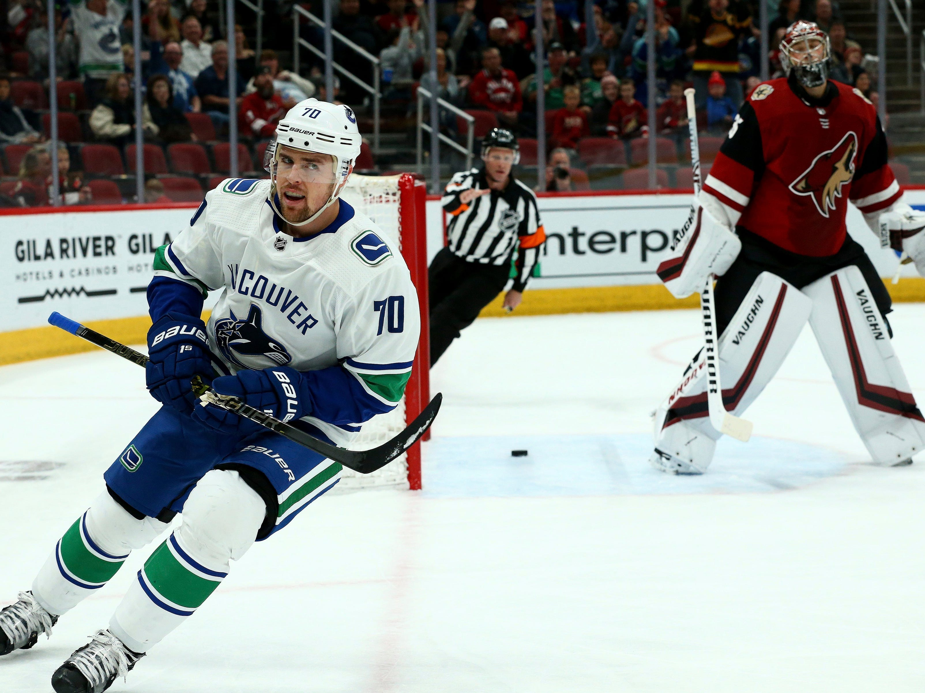 Vancouver Canucks left wing Tanner Pearson (70) skates past after scoring a goal against Arizona Coyotes goaltender Darcy Kuemper, right, during the first period of an NHL hockey game Thursday, Feb. 28, 2019, in Glendale, Ariz.