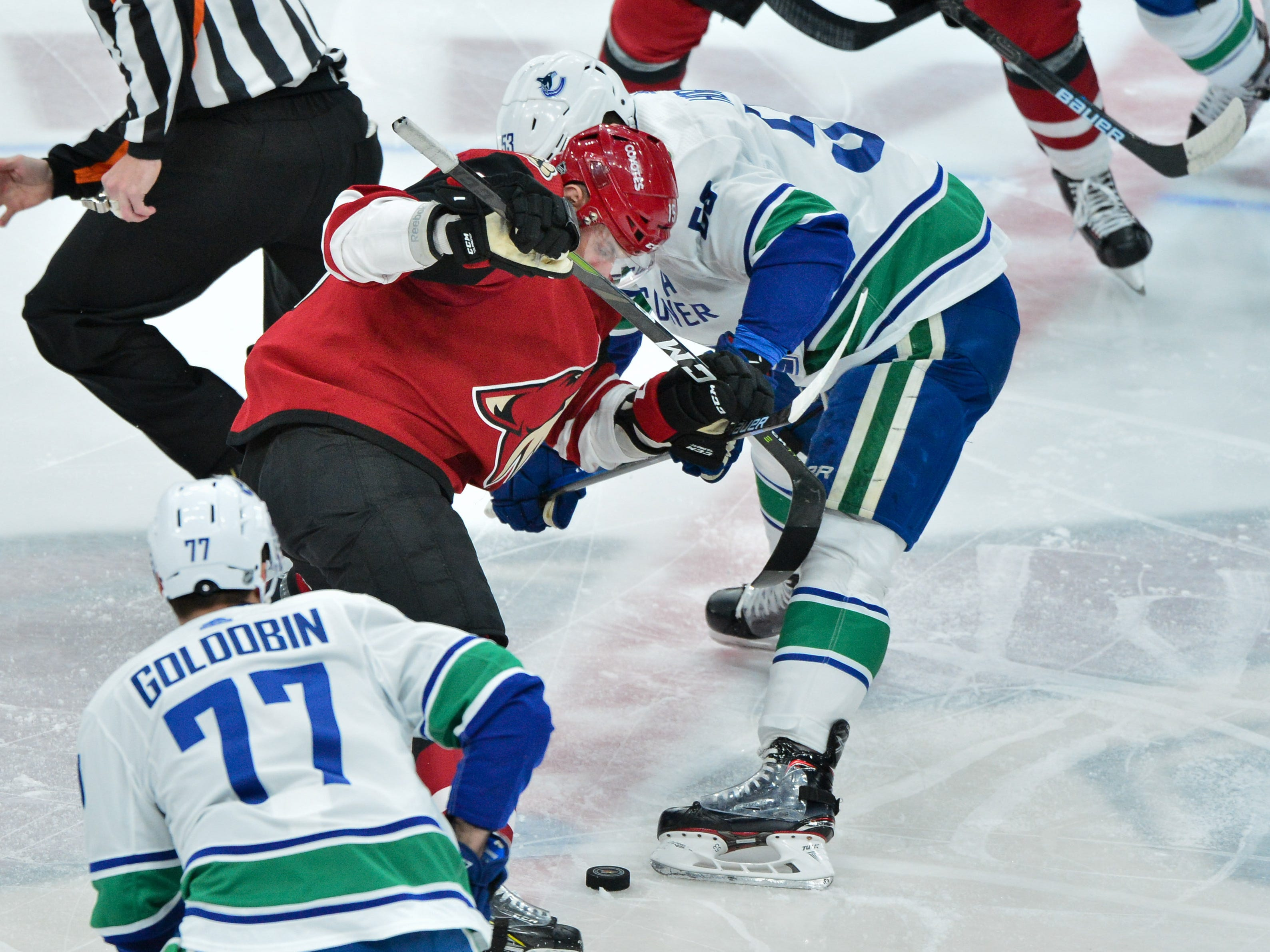 Feb 28, 2019; Glendale, AZ, USA; Arizona Coyotes center Brad Richardson (15) and Vancouver Canucks center Bo Horvat (53) battle for a face-off in the first period at Gila River Arena.