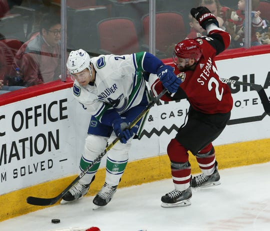 Coyotes center Derek Stepan battles with Canucks defenseman Luke Schenn  during a game Feb. 28 at Gila River Arena.