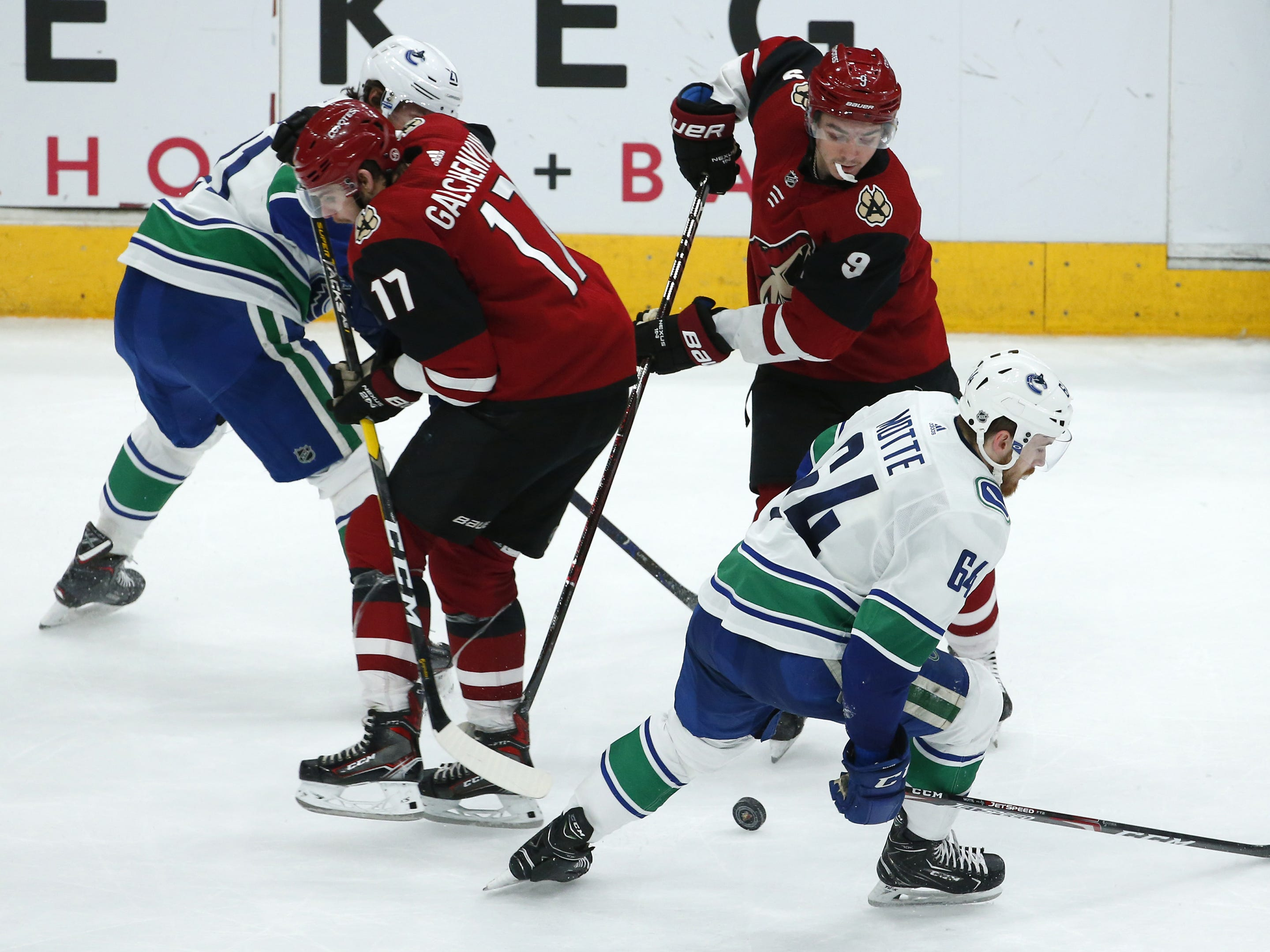 Arizona Coyotes center Clayton Keller (9) battles Vancouver Canucks center Tyler Motte (64) for the puck during a NHL game at Gila River Arena in Glendale on February 28.