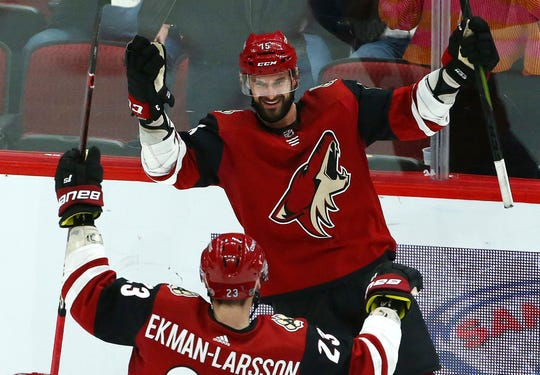 Arizona Coyotes center Brad Richardson (15) smiles as he celebrates his hat trick against the Vancouver Canucks with defenseman Oliver Ekman-Larsson (23) during the second period of an NHL hockey game Thursday, Feb. 28, 2019, in Glendale, Ariz.