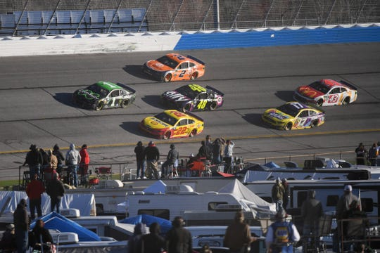Joey Logano (22) leads the pack as cars go three-wide into a turn at the Folds of Honor QuickTrip 500 at Atlanta Motor Speedway.