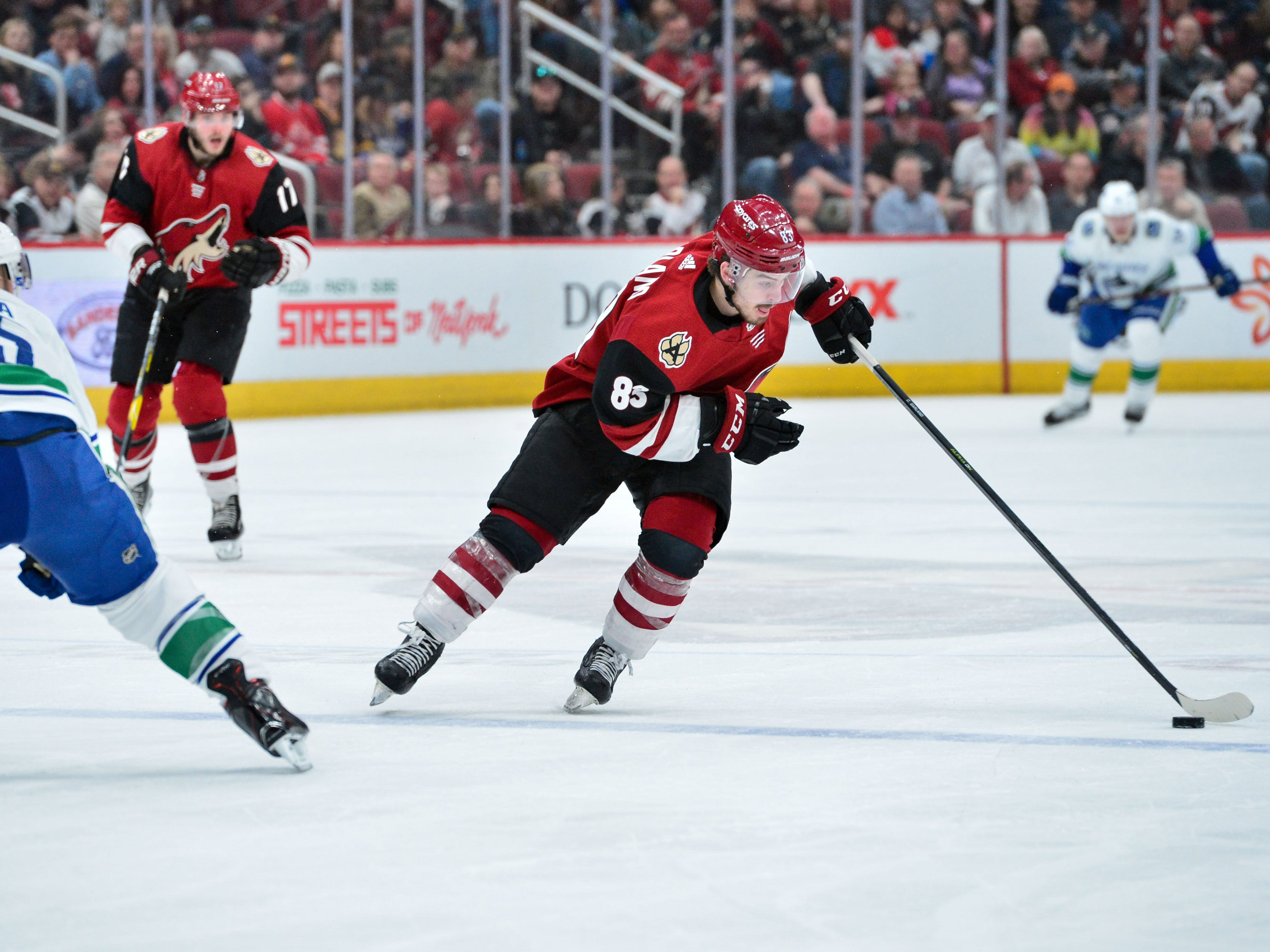 Feb 28, 2019; Glendale, AZ, USA; Arizona Coyotes right wing Conor Garland (83) skates with the puck as Vancouver Canucks defenseman Alex Biega (55) defends during the second period at Gila River Arena.