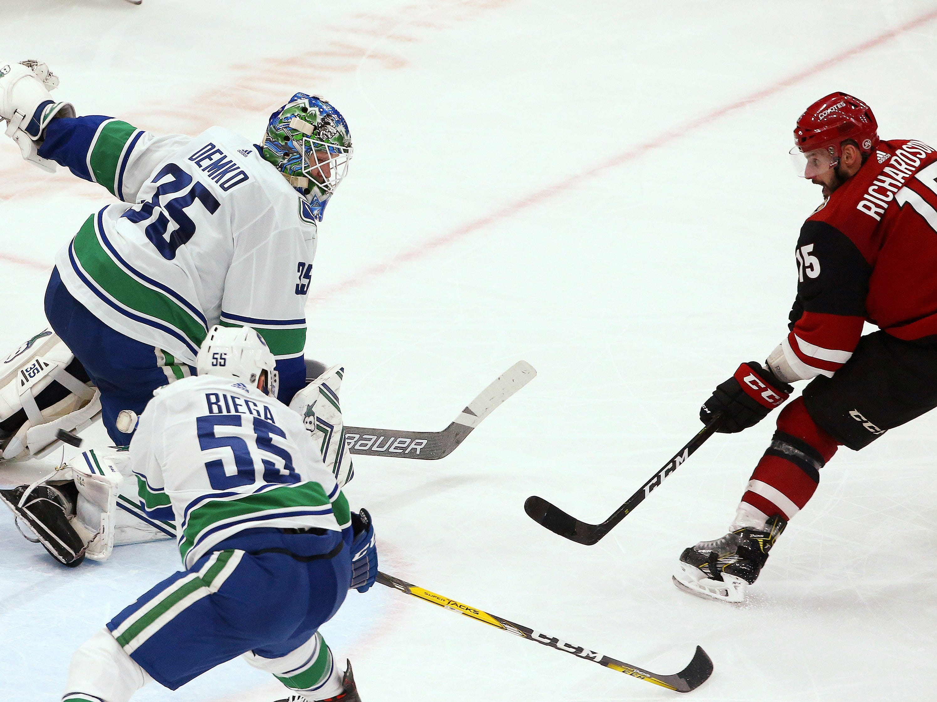 Arizona Coyotes center Brad Richardson, right, sends the puck past Vancouver Canucks goaltender Thatcher Demko (35) and defenseman Alex Biega (55) for a goal, to earn a hat trick during the second period of an NHL hockey game Thursday, Feb. 28, 2019, in Glendale, Ariz.