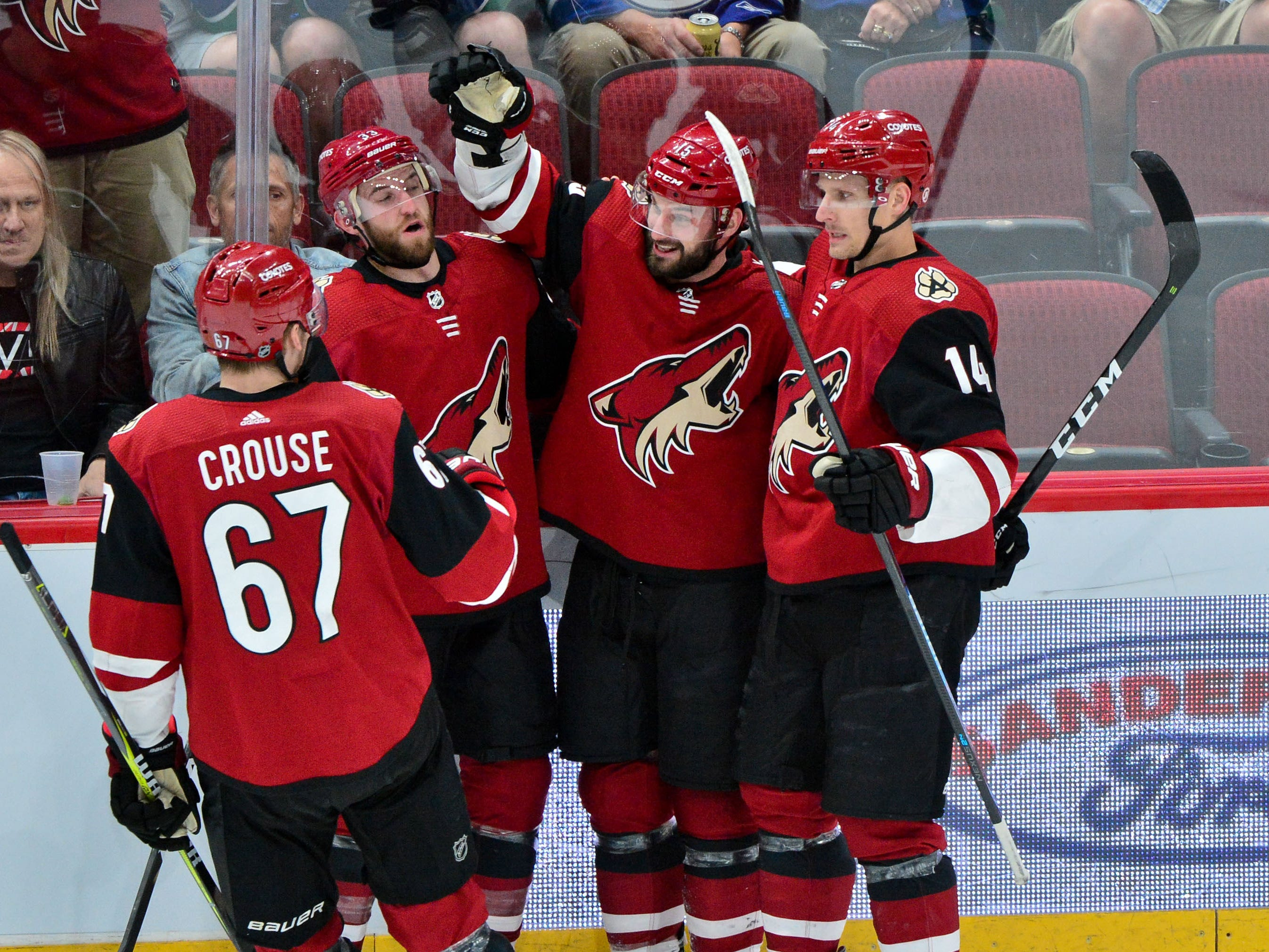 Feb 28, 2019; Glendale, AZ, USA; Arizona Coyotes center Brad Richardson (15) celebrates with defenseman Alex Goligoski (33), left wing Lawson Crouse (67) and right wing Richard Panik (14) after scoring a goal in the first period against the Vancouver Canucks at Gila River Arena.