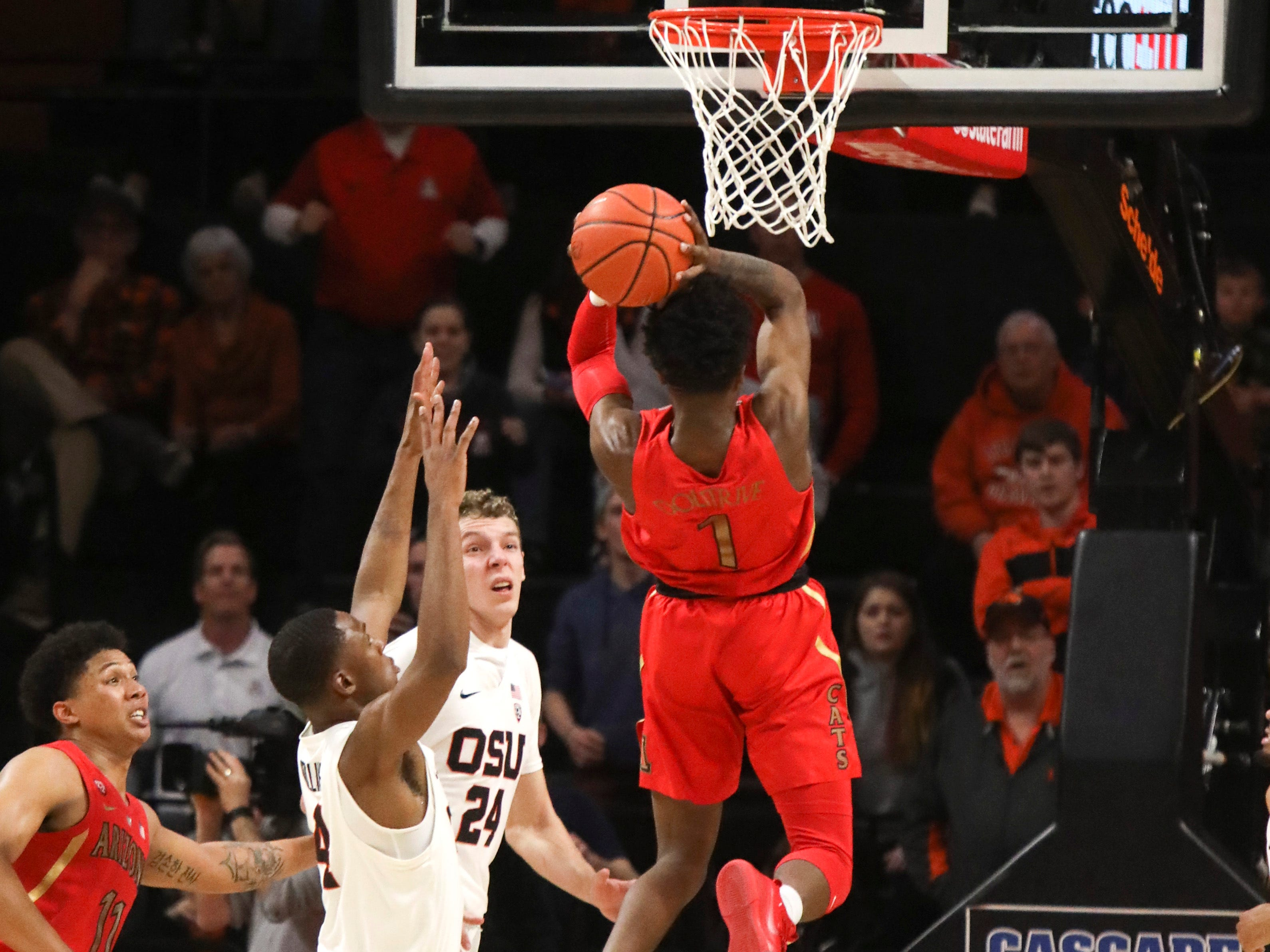 Arizona's Devonaire Doutrive (1) scores off a rebound in the final second of the game, getting past Oregon State's Alfred Hollins (4) and Kylor Kelley (24), to secure the win during an NCAA college basketball game in Corvallis, Ore., Thursday, Feb. 28, 2019. Arizona won 74-72.
