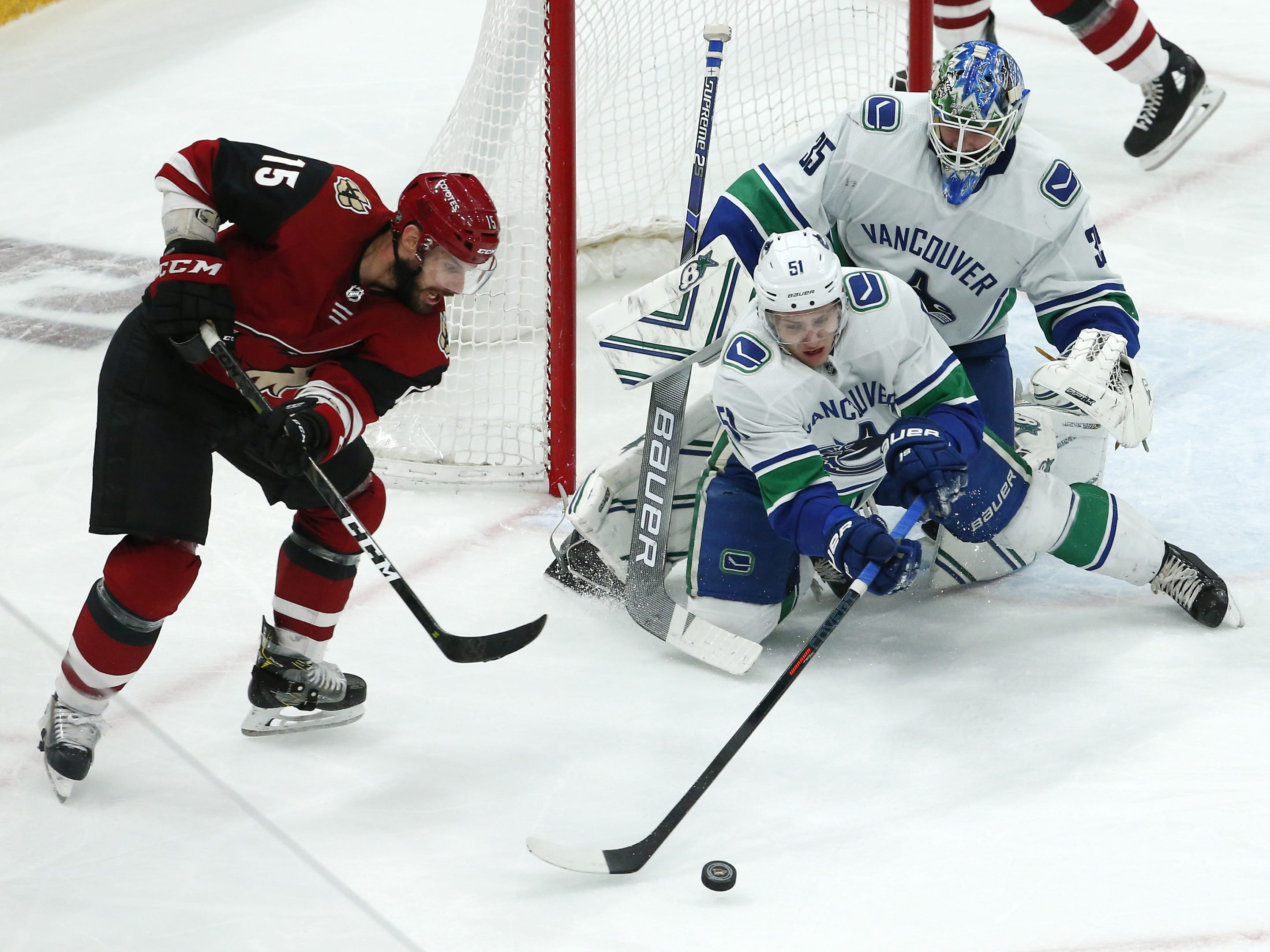 Arizona Coyotes center Brad Richardson (15) battles Vancouver Canucks defenseman Troy Stecher (51) for the puck during a NHL game at Gila River Arena in Glendale on February 28.