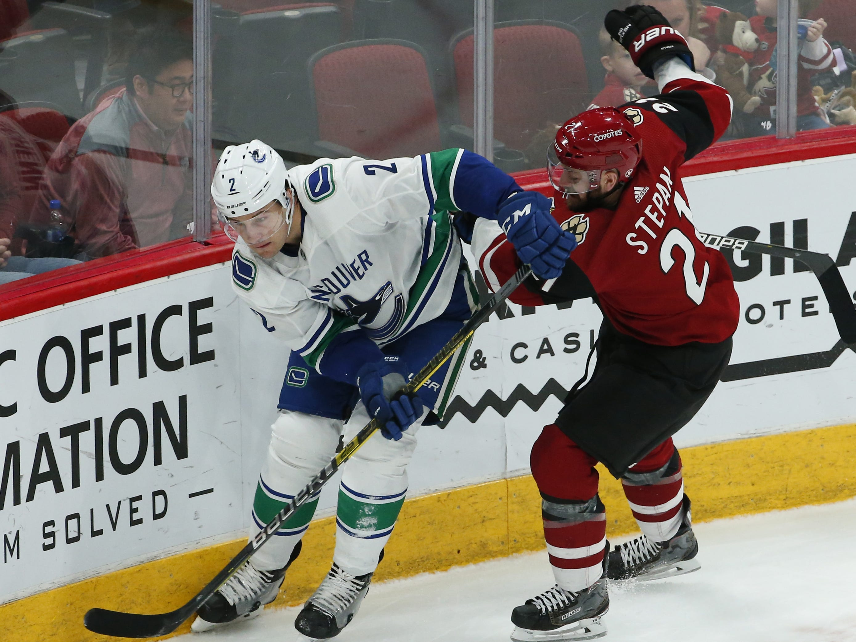 Vancouver Canucks defenseman Luke Schenn (2) battles Arizona Coyotes center Derek Stepan (21)  for the puck during a NHL game at Gila River Arena in Glendale on February 28.