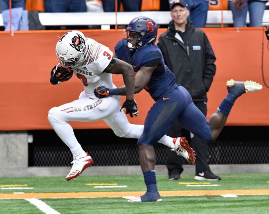 N.C. State receiver Kelvin Harmon tries to break a tackle by Syracuse defensive back Evan Foster after making a catch during the fourth quarter of a game Oct. 27 at the Carrier Dome.