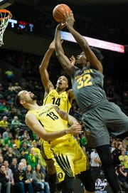 Feb 28, 2019; Eugene, OR, USA; Arizona State Sun Devils forward De'Quon Lake (32) shoots the ball as Oregon Ducks forward Paul White (13) and forward Kenny Wooten (14) defend during the first half at Matthew Knight Arena.