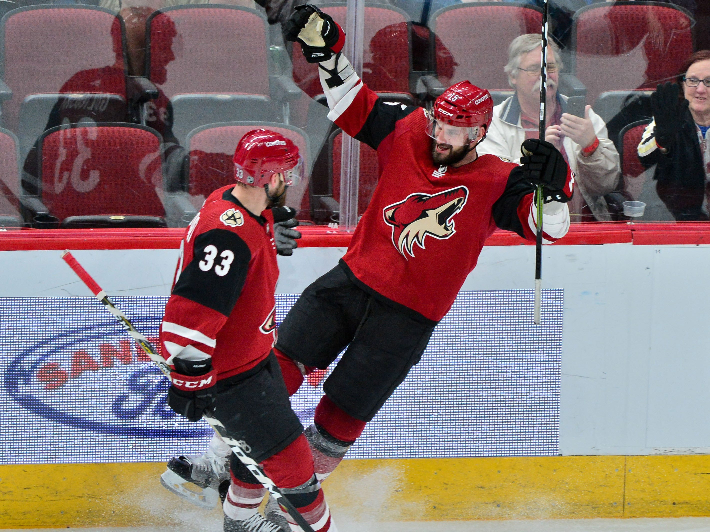 Feb 28, 2019; Glendale, AZ, USA; Arizona Coyotes center Brad Richardson (15) celebrates with defenseman Alex Goligoski (33) after scoring a goal in the first period against the Vancouver Canucks at Gila River Arena.