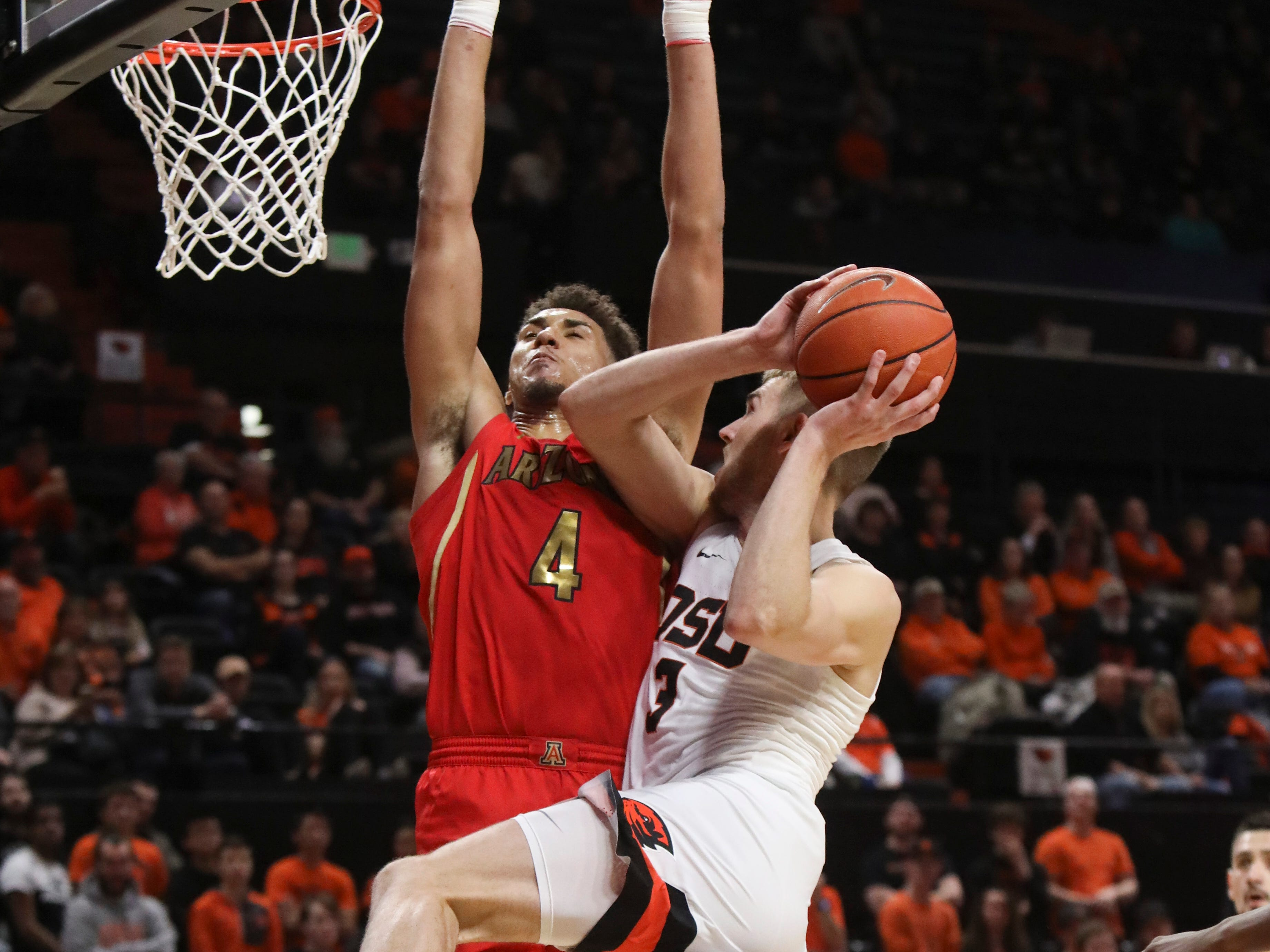 Arizona's Chase Jeter (4) tries to block a shot by Oregon State's Tres Tinkle (3) during the first half of an NCAA college basketball game in Corvallis, Ore., Thursday, Feb. 28, 2019.