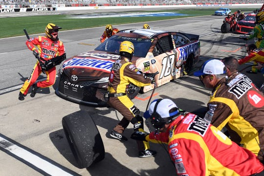 Kyle Busch's crew tends to his No. 18 car during a pitstop at the Folds of Honor QuickTrip 500 at Atlanta Motor Speedway.