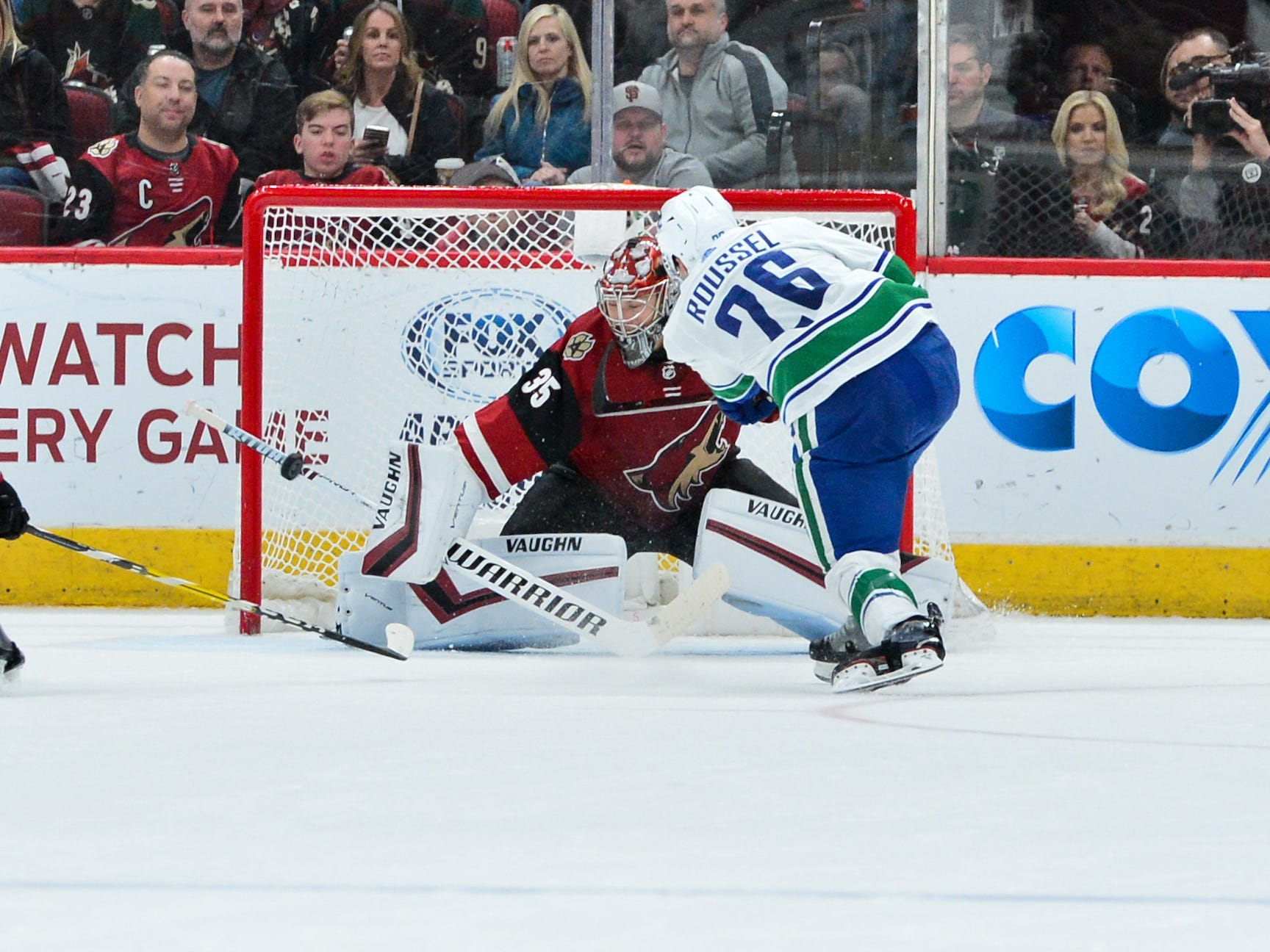 Feb 28, 2019; Glendale, AZ, USA; Arizona Coyotes goaltender Darcy Kuemper (35) makes a save on Vancouver Canucks left wing Antoine Roussel (26) during the second period at Gila River Arena.