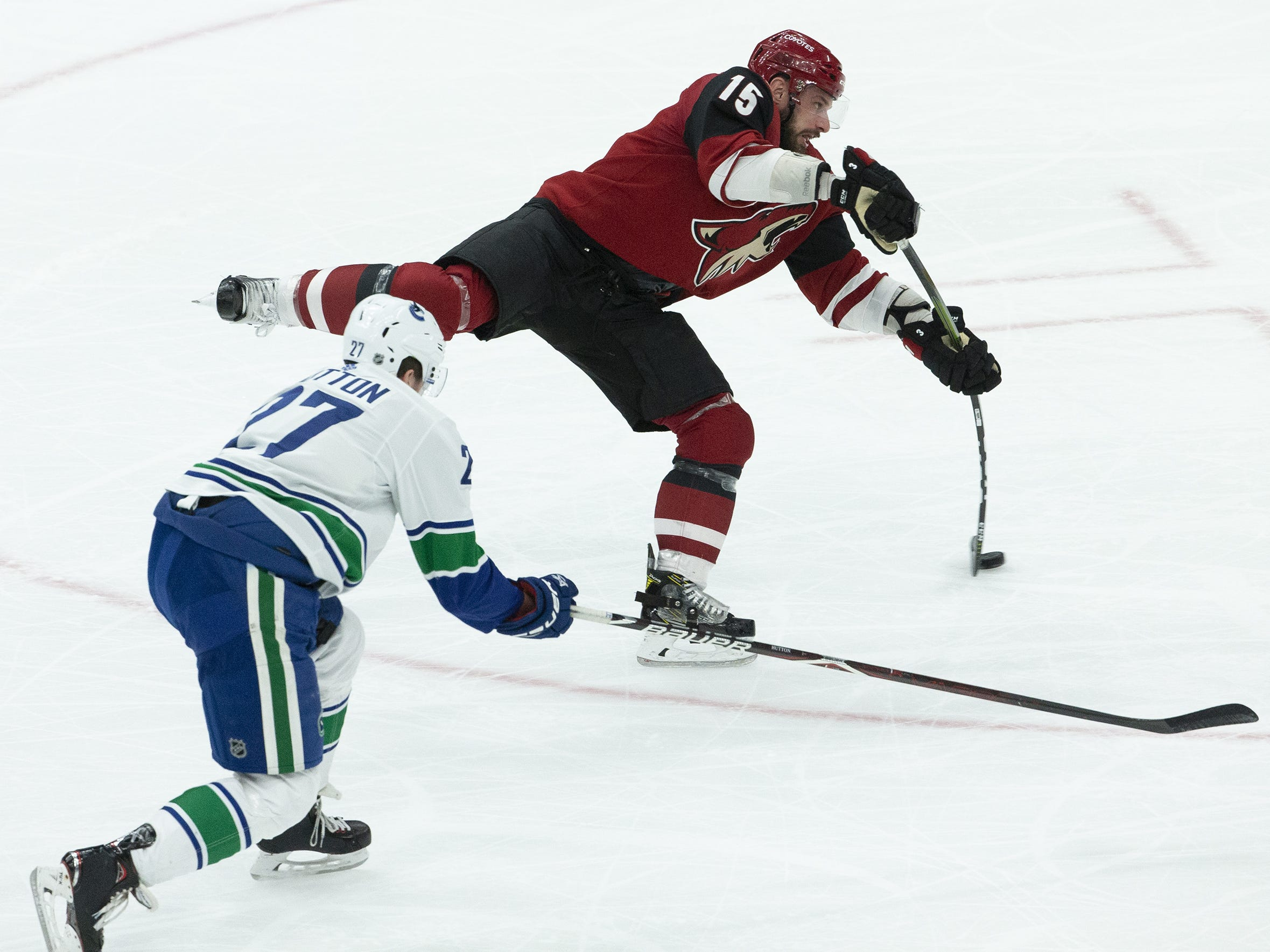 Arizona Coyotes center Brad Richardson (15) shoots for a goal while being defended by Vancouver Canucks defenseman Ben Hutton (27) during a NHL game at Gila River Arena in Glendale on February 28.