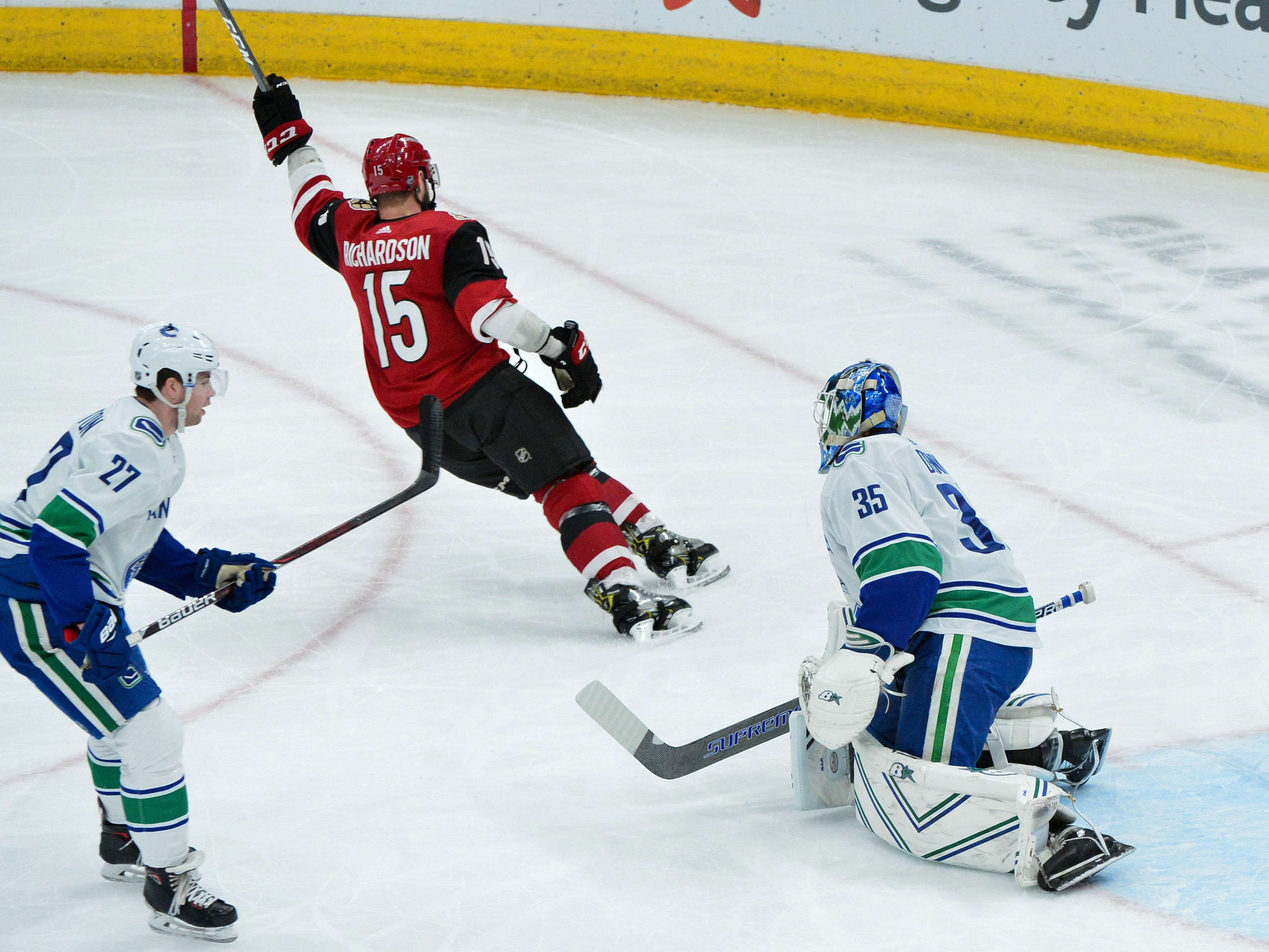 Feb 28, 2019; Glendale, AZ, USA; Arizona Coyotes center Brad Richardson (15) celebrates after scoring a goal past Vancouver Canucks goaltender Thatcher Demko (35) and defenseman Ben Hutton (27)  during the first period at Gila River Arena.