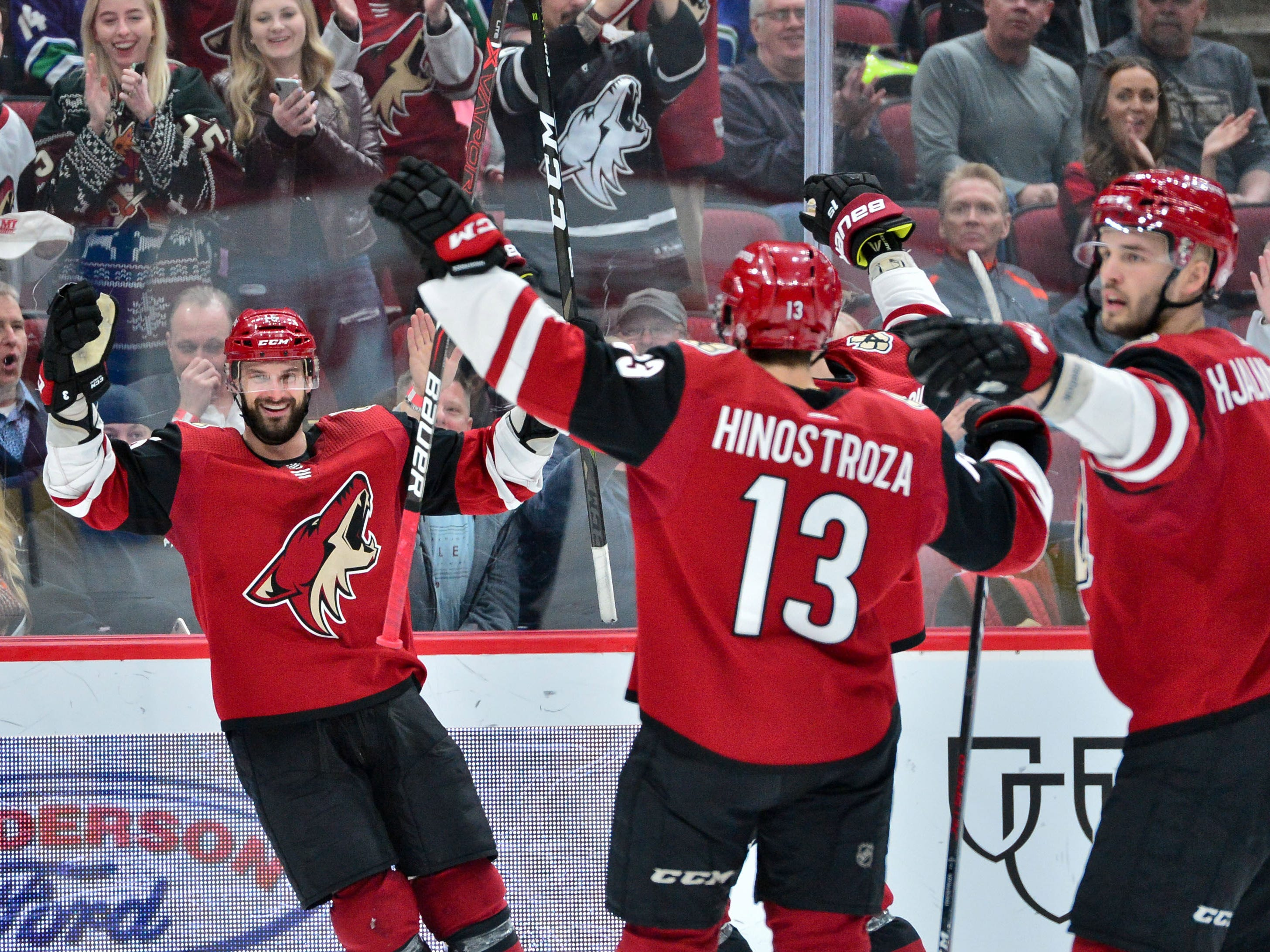 Feb 28, 2019; Glendale, AZ, USA; Arizona Coyotes center Brad Richardson (15) celebrates with center Vinnie Hinostroza (13) and defenseman Niklas Hjalmarsson (4) after scoring his third goal on the game during the second period against the Vancouver Canucks at Gila River Arena.