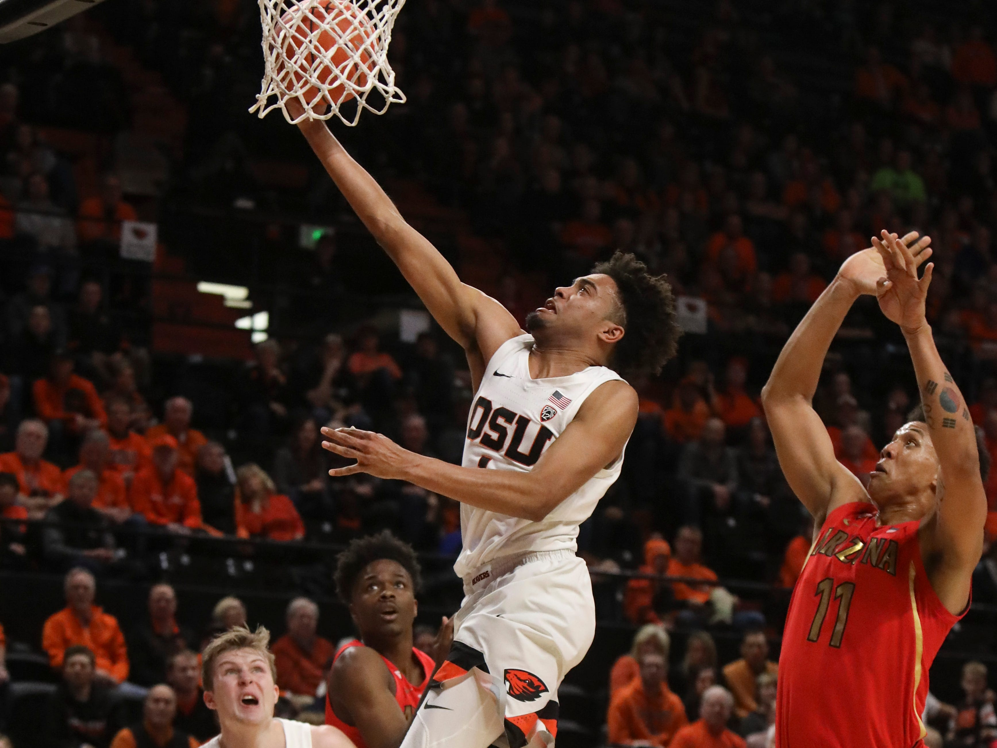 Oregon State's Stephen Thompson Jr. (1) drives to the basket past Arizona's Ira Lee, right, as Oregon State's Zach Reichle, left, and Arizona's Devonaire Doutrive (1) watch during the second half of an NCAA college basketball game in Corvallis, Ore., Thursday, Feb. 28, 2019. Arizona won 74-72.