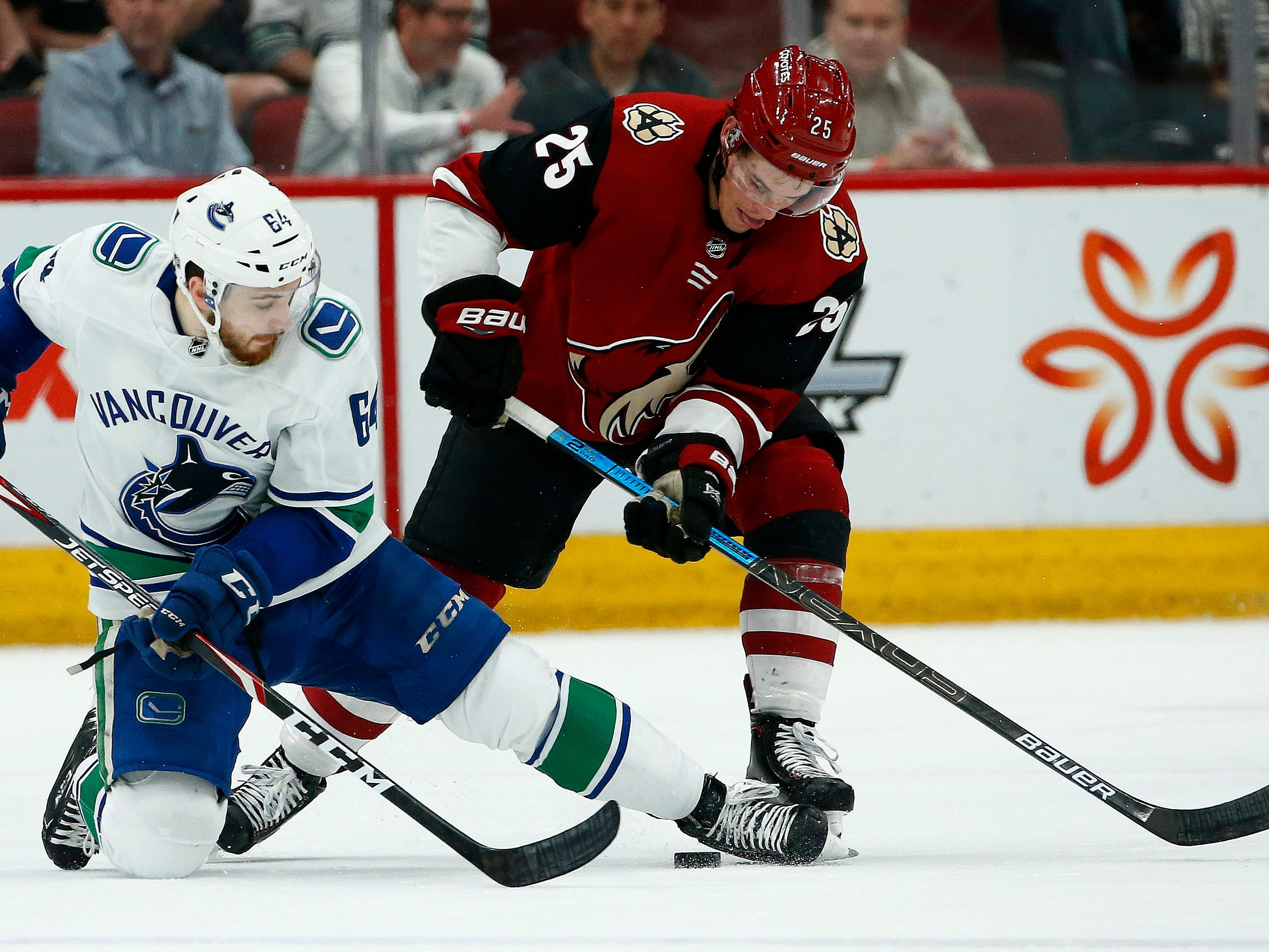 Vancouver Canucks center Tyler Motte (64) battles with Arizona Coyotes center Nick Cousins (25) for the puck during the first period of an NHL hockey game Thursday, Feb. 28, 2019, in Glendale, Ariz.