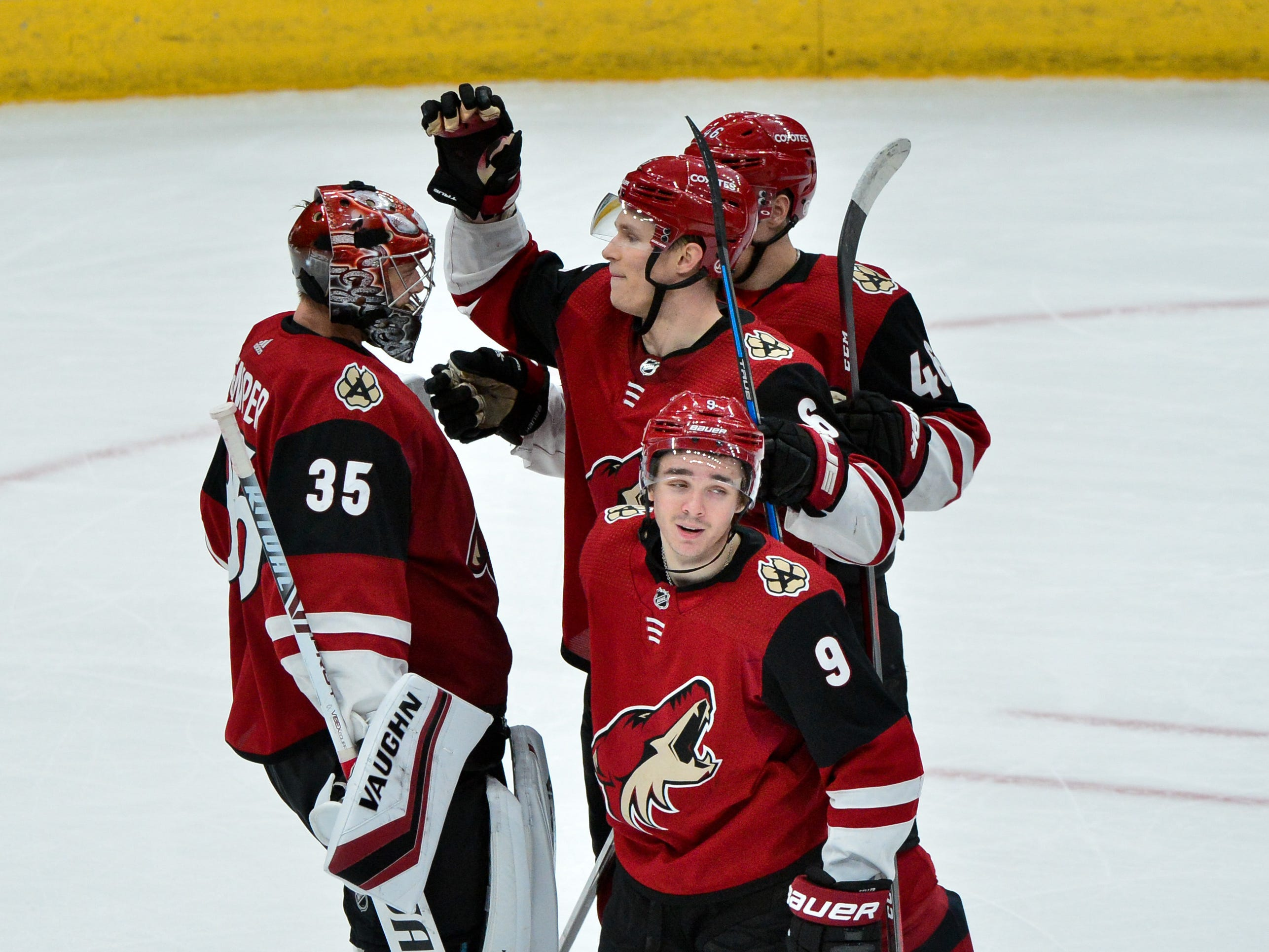 Feb 28, 2019; Glendale, AZ, USA; Arizona Coyotes goaltender Darcy Kuemper (35) celebrates with center Clayton Keller (9), defenseman Jakob Chychrun (6) and defenseman Ilya Lyubushkin (46) after defeating the Vancouver Canucks at Gila River Arena.