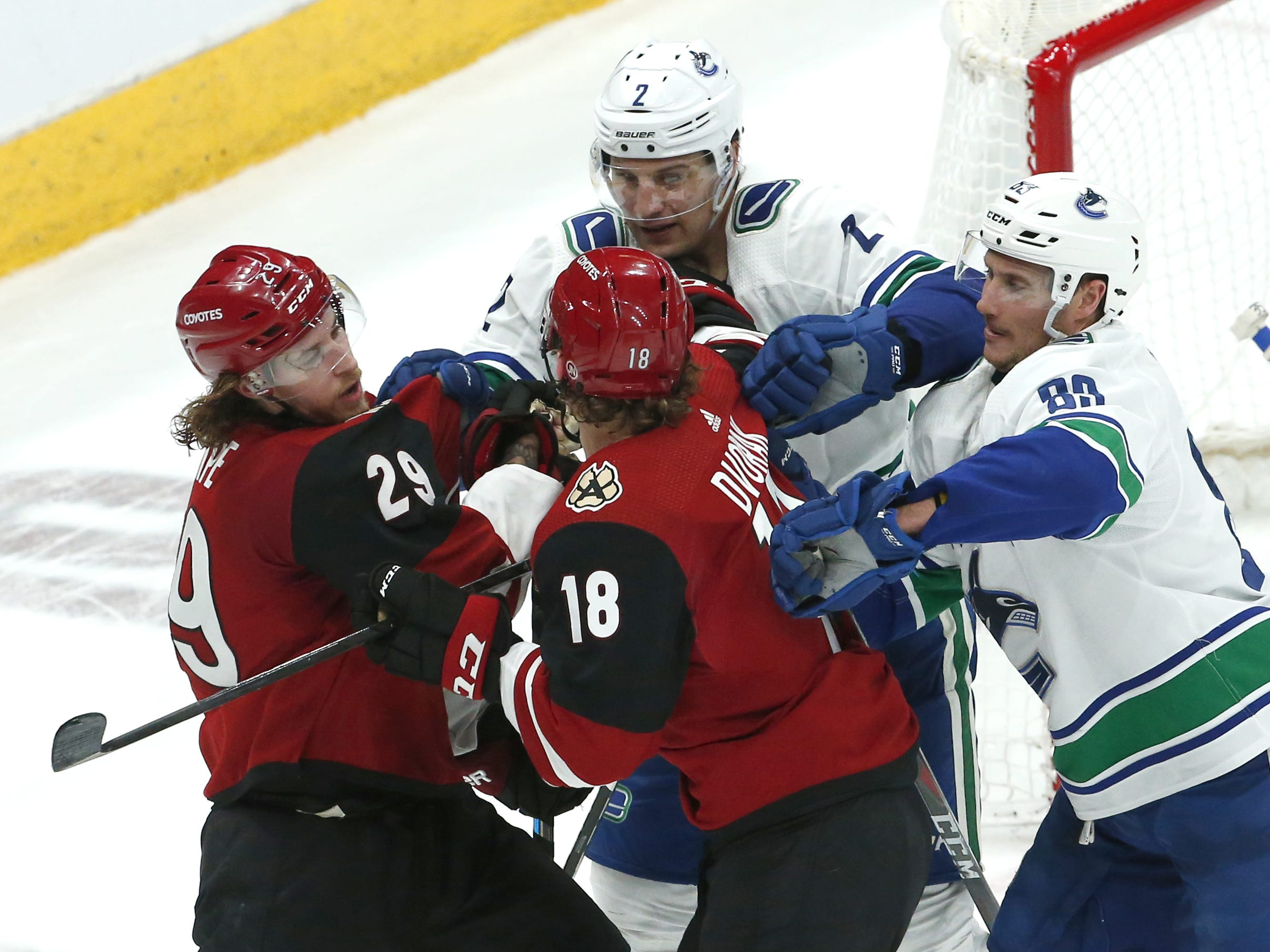 Arizona Coyotes right wing Mario Kempe (29) and center Christian Dvorak (18) get into a little pushing and shoving match with Vancouver Canucks defenseman Luke Schenn (2) and center Jay Beagle (83) during a NHL game at Gila River Arena in Glendale on February 28.