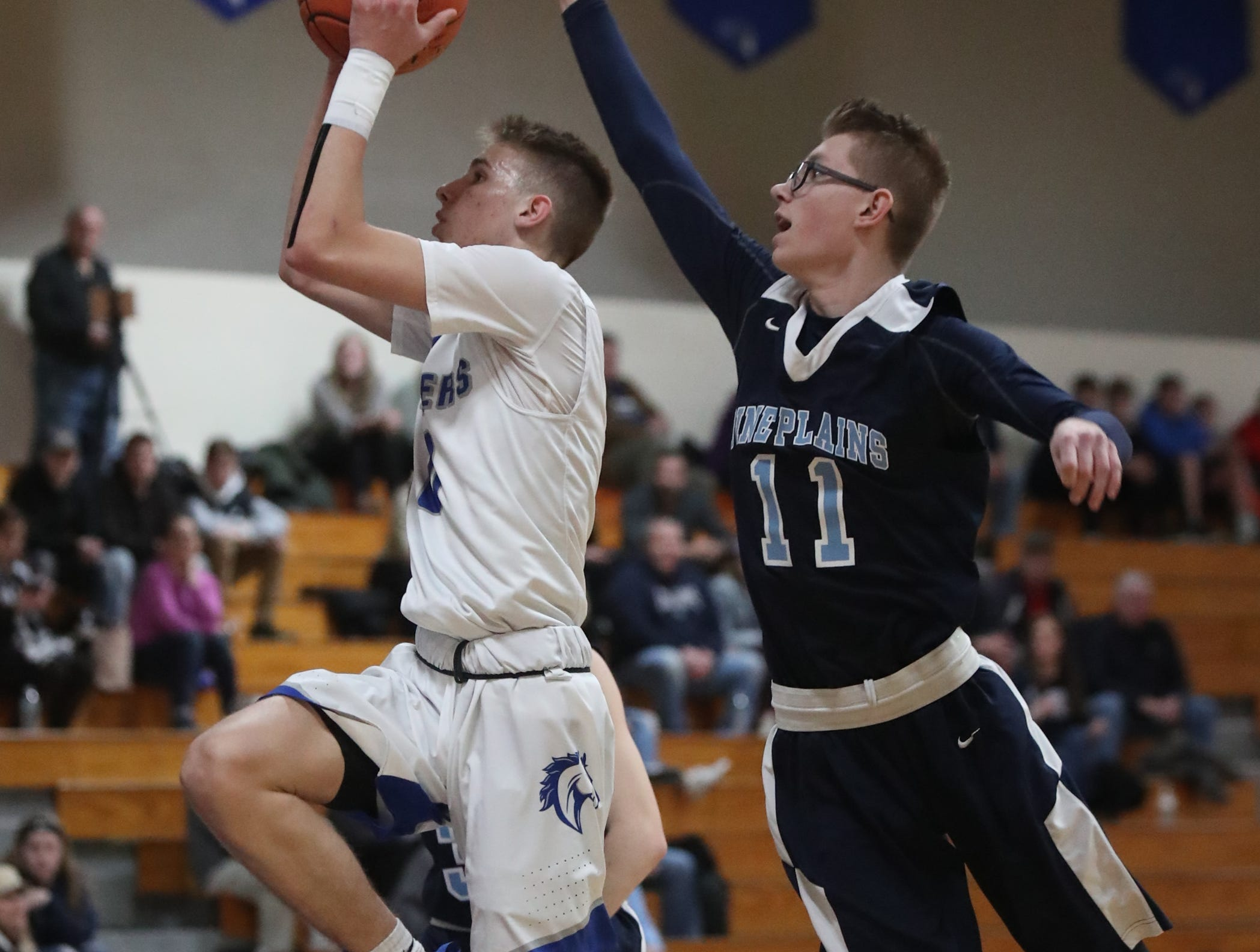 Millbrook's Jake Daly (0) puts up a shot past Pine Plains' Kane Kozlowski (11) in the boys basketball Class C section final basketball game at Mount St. Mary College in Newburgh on Thursday, February 28, 2019.
