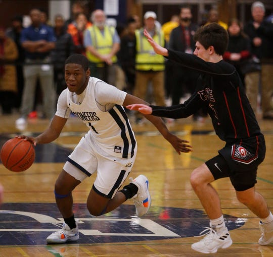 Poughkeepsie's Jamik Carter drives against a Rye defender during a Section 1 Class A semifinal Feb. 28.