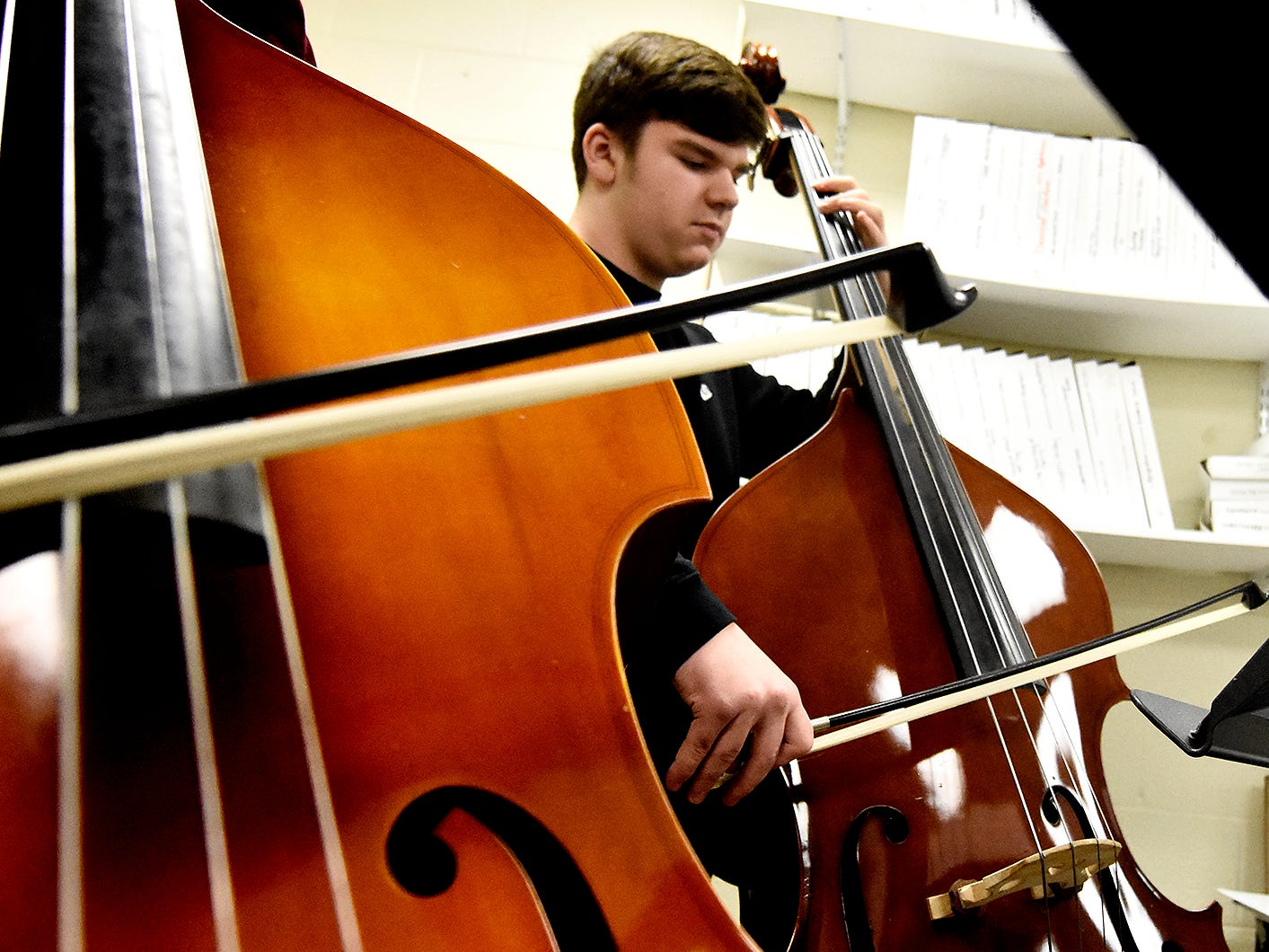 """Red Lion High School orchestra bassist Scott Stover, a freshman, plays adjacent to junior Micah Sumwalt during an orchestra rehearsal at the school Friday, March 1, 2019. The orchestra is fine-tuning """"Obsidian Rainbow"""" which was written by Red Lion graduate and New York composer Derek Cooper. He is premiering the piece via the Red Lion Area High School string orchestra on Wednesday, March 6. Cooper will be at the school working with the orchestra beforehand. Bill Kalina photo"""