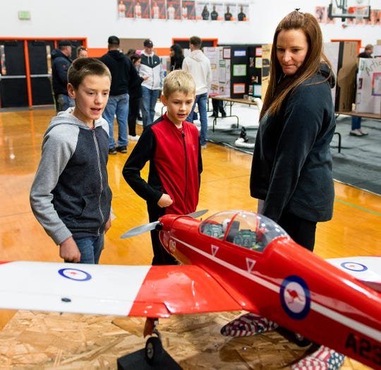 (From left) Dylan, Lukas and Lea Jensen admire one of the model airplanes on display.