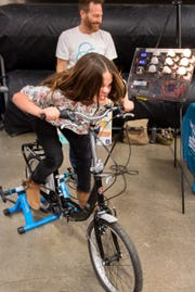 Abby Edwards pedals a bicycle, trying to generate power to light a display of bulbs.