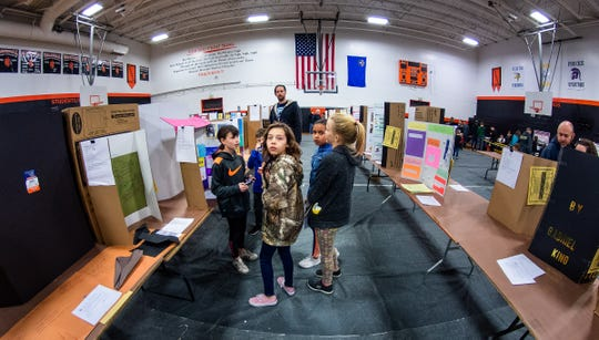 Kids view some of the many exhibits on display in the gymnasium.