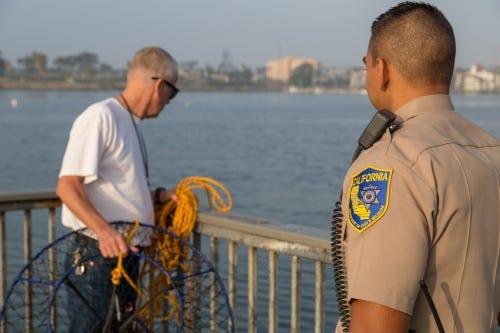 Wildlife officer and hoop-netter on pier.