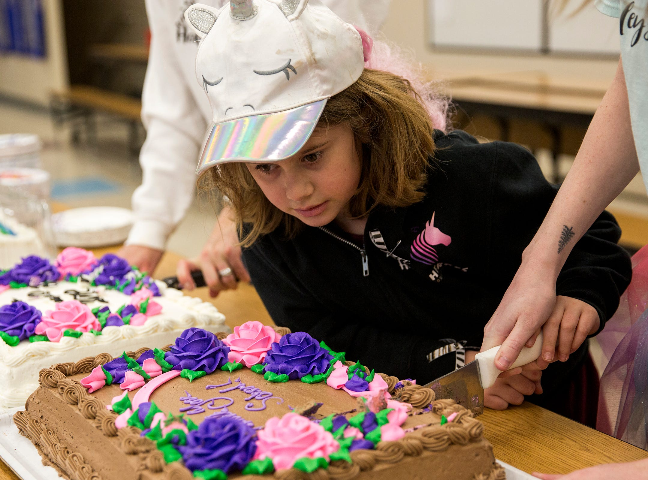 Haley Pollman, a third grader, helps serve cake on rare disease day at Lee Elementary School in Salem on Thursday, Feb. 28, 2019. A fundraiser at Lee recently raised $1,700 for Batten disease which Haley has.