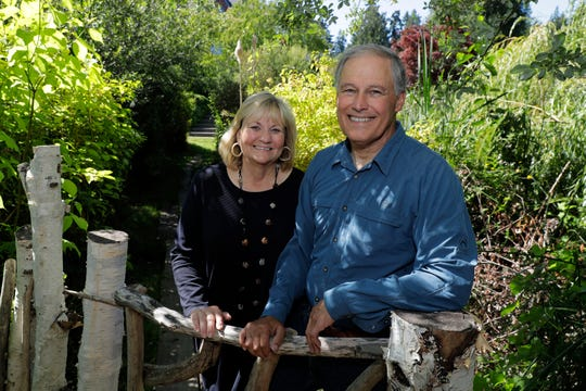 In this file photo taken July 23, 2018, Washington Gov. Jay Inslee poses for a photo with his wife, Trudi Inslee, on a path near their home on Bainbridge Island, Wash.