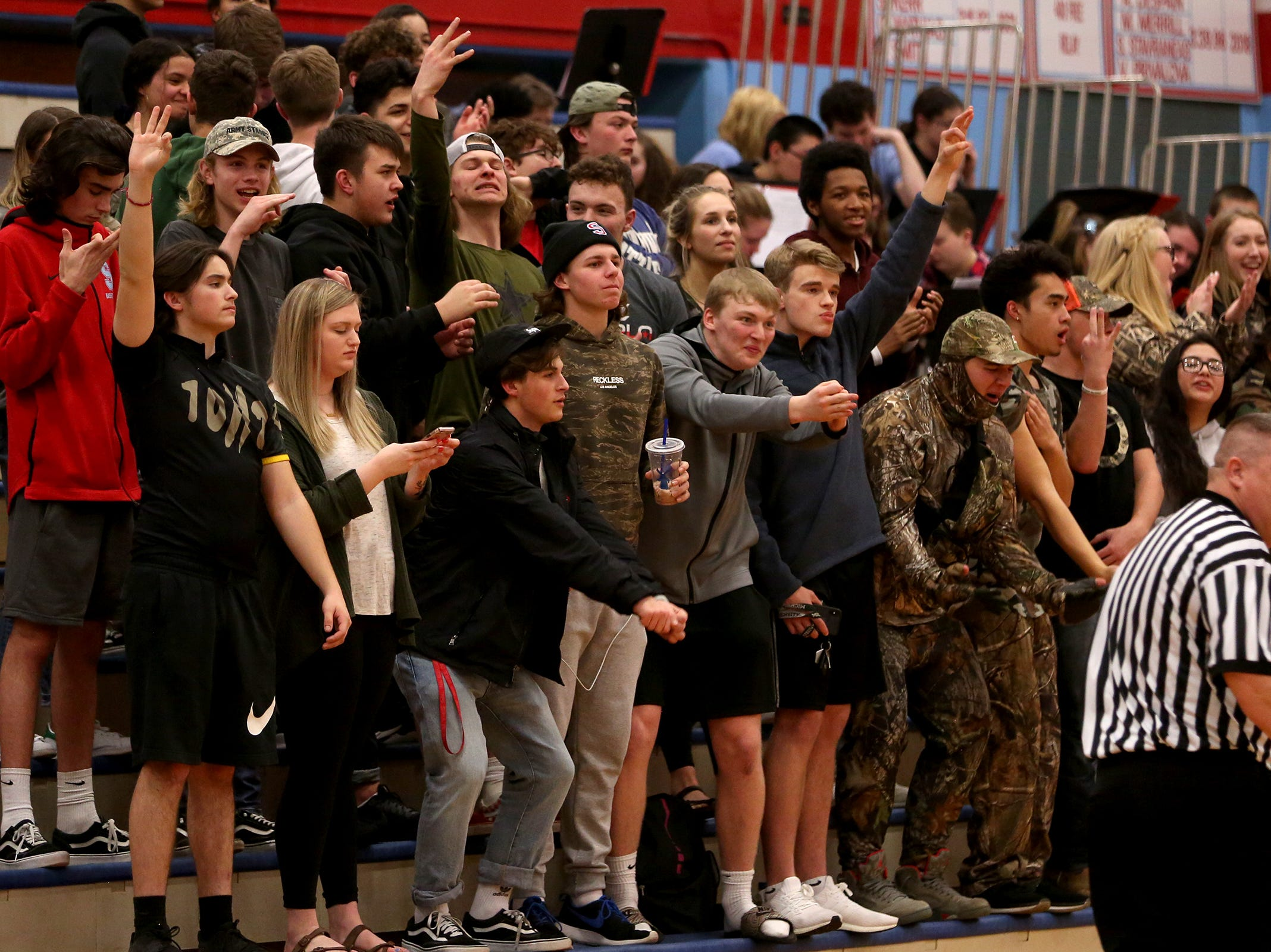 South Salem's students, dressed in camouflage, cheer on their team during the South Salem vs. Mountainside girls basketball OSAA playoff game in Salem on Thursday, Feb. 28, 2019.