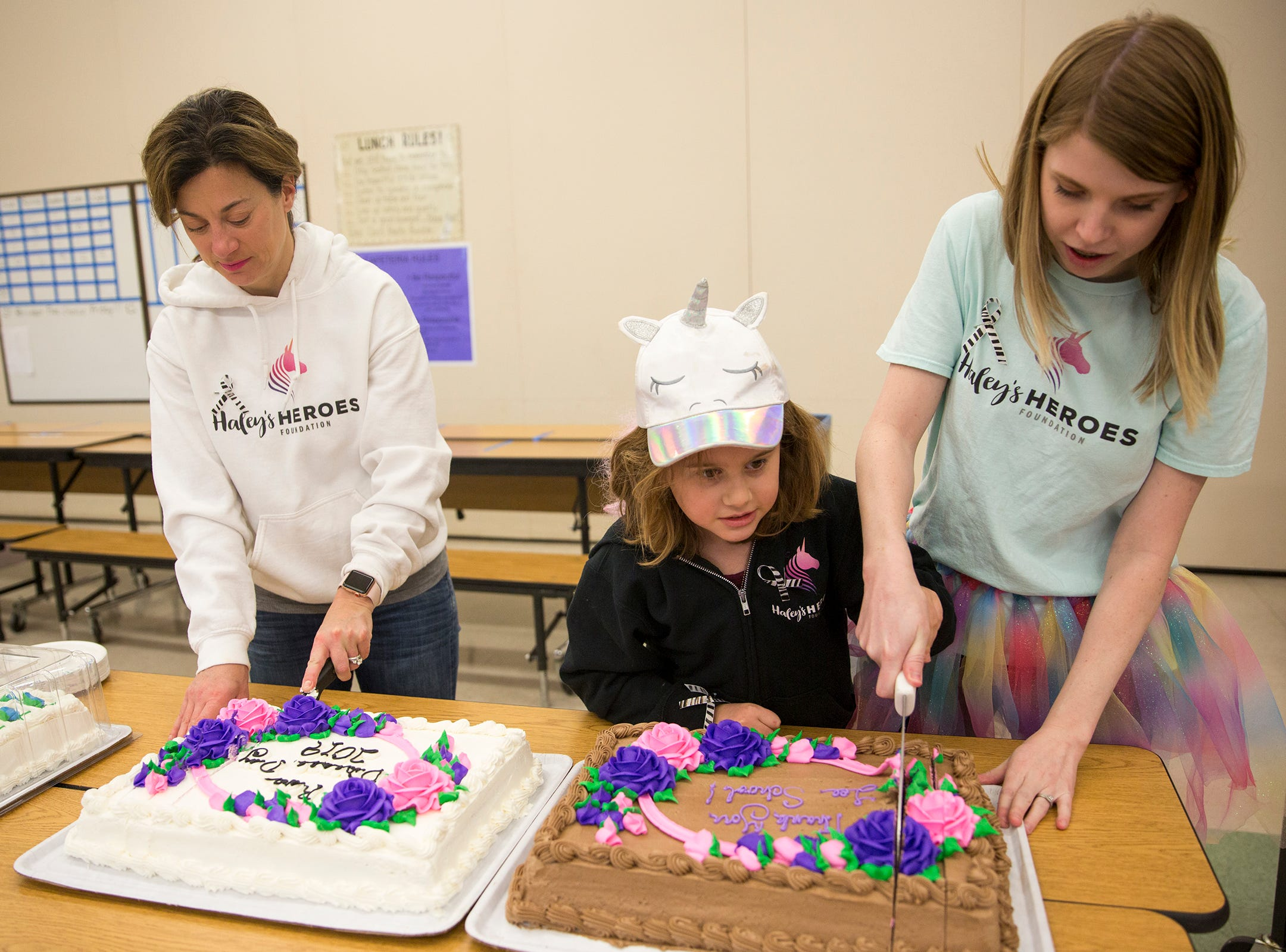 Haley Pollman, her mother Melissa Pollman (left) and instructional assistant Nichele Coria (right) cut cake for students on rare disease day at Lee Elementary School in Salem on Thursday, Feb. 28, 2019.