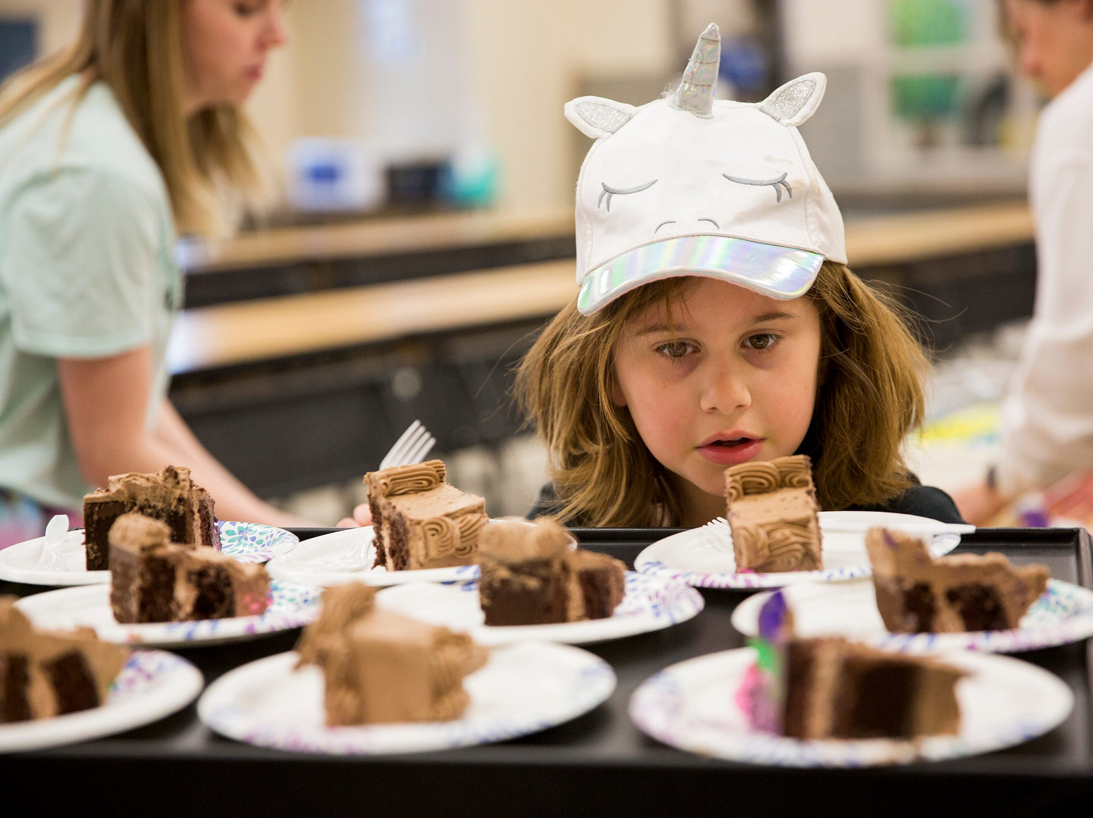 Haley Pollman, a third grader, helps place forks on plates of cake on rare disease day at Lee Elementary School in Salem on Thursday, Feb. 28, 2019. A fundraiser at Lee recently raised $1,700 for Batten disease which Haley has.