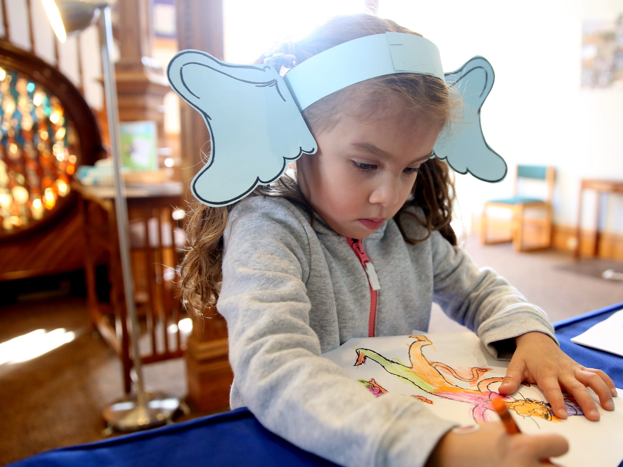 """Clara Prickett, 4, of Salem, wears ears like Horton from """"Horton Hears a Who"""" and colors as part of a National Read Across America Day activity in honor of Dr. Seuss' birthday at Gilbert House Children's Museum in Salem  on Friday, March 1, 2019."""