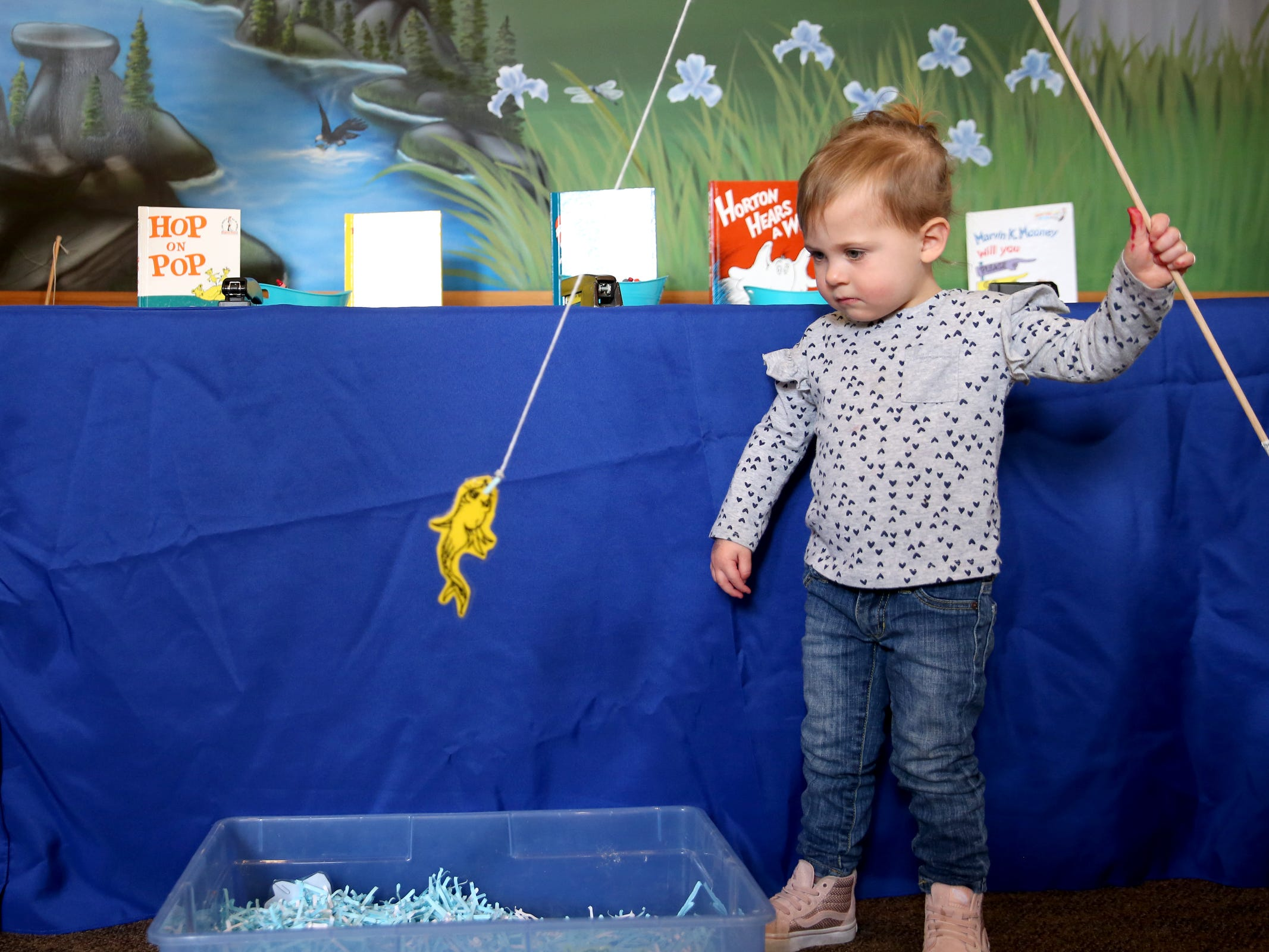 """Jaelynn Slaezak, 2, of Salem, plays a fishing game, an homage to """"One Fish, Two Fish, Red Fish, Blue Fish"""", as part of a National Read Across America Day activity in honor of Dr. Seuss' birthday at Gilbert House Children's Museum in Salem  on Friday, March 1, 2019."""