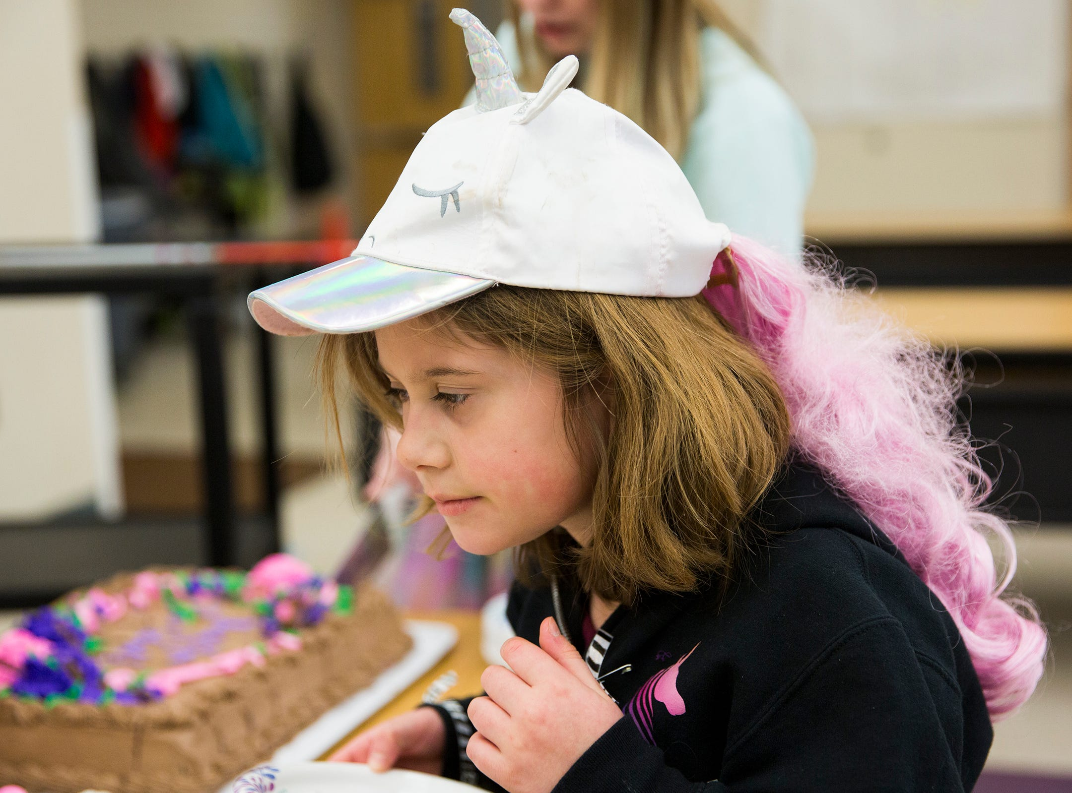 Haley Pollman, a third grader, helps serve cake on rare disease day at Lee Elementary School in Salem on Thursday, Feb. 28, 2019.