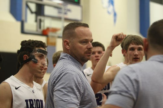 Irion County boys basketball head coach John Morrow, center, listens to an assistant coach in the huddle of a regional quarterfinal game Feb. 26, 2019, at Lake View High School.