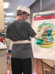 Zachary Sutterfield paints in the Brooke Army Medical Center in San Antonio. Sutterfield sustained nearly 70 percent burns, head trauma, and underwent numerous surgeries. He continues to recover in the Brooke Army Medical Center - Fisher House with his family.
