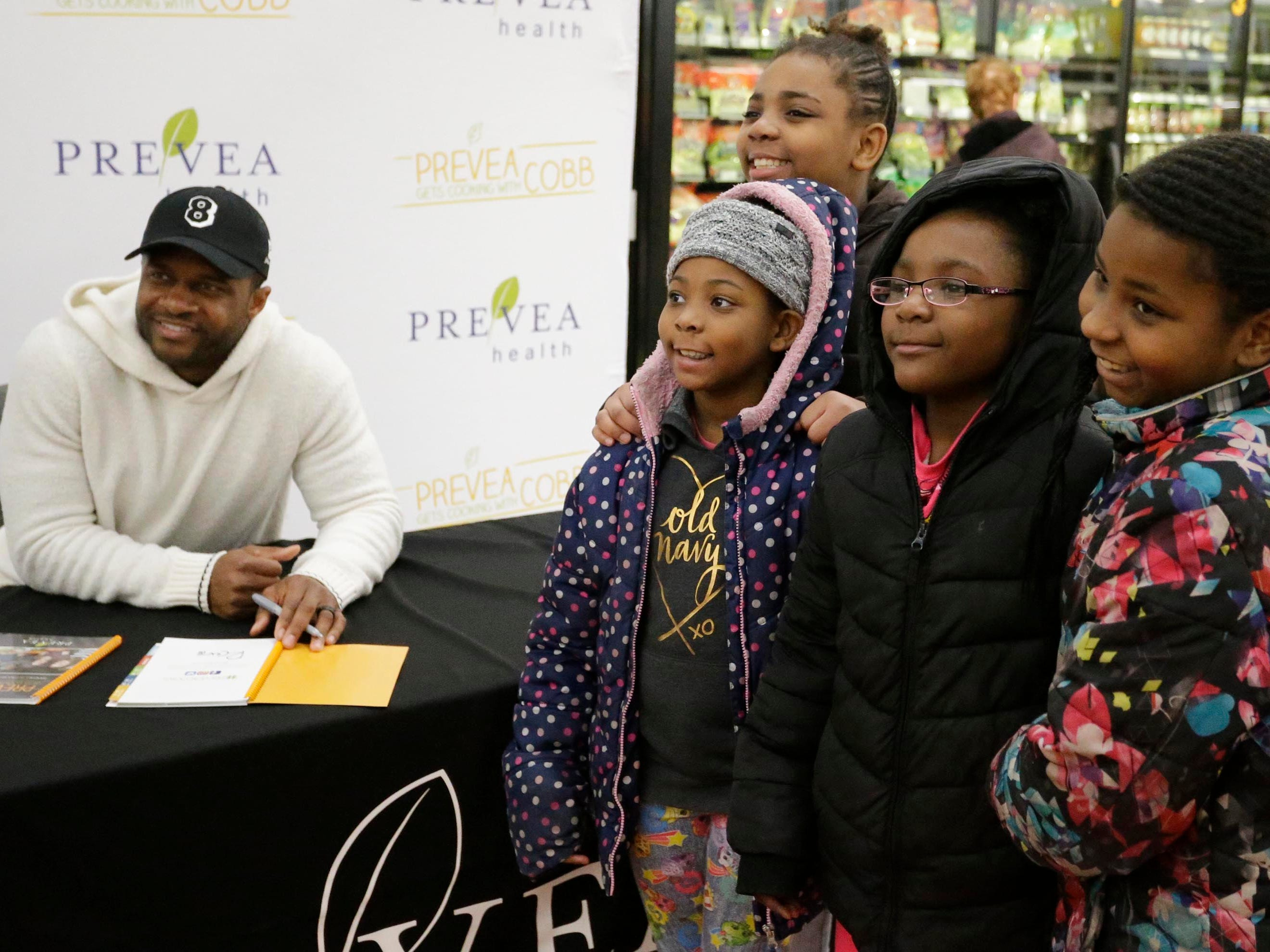 """A family smiles with Green Bay Packer Randall Cobb at Festival Foods, Thursday, February 28, 2019, in Sheboygan, Wis. Cobb signed his book called, """"Prevea Gets Cooking with Cobb: Randall's Favorite Kid-Friendly Recipes""""."""