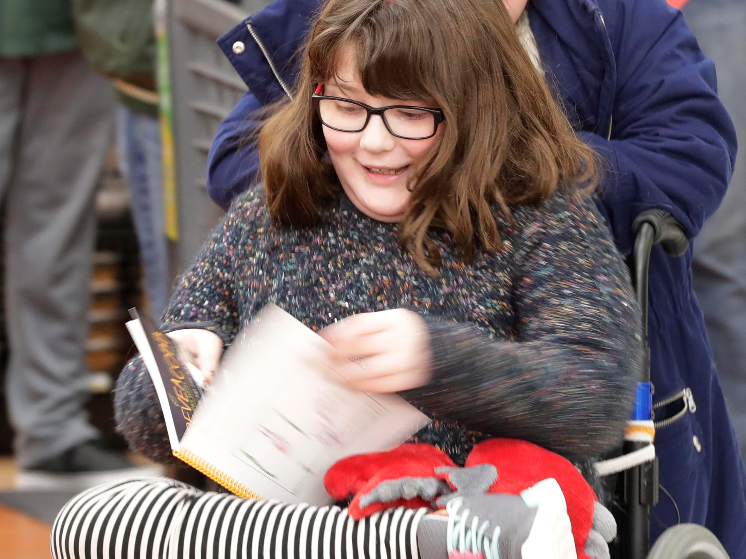 Lorelai Burke, 10, of Sheboygan, smiles at the cookbook she had signed by Green Bay Packer Randall Cobb at Festival Foods, Thursday, February 28, 2019, in Sheboygan, Wis. Burke suffers from brittle bone disease.