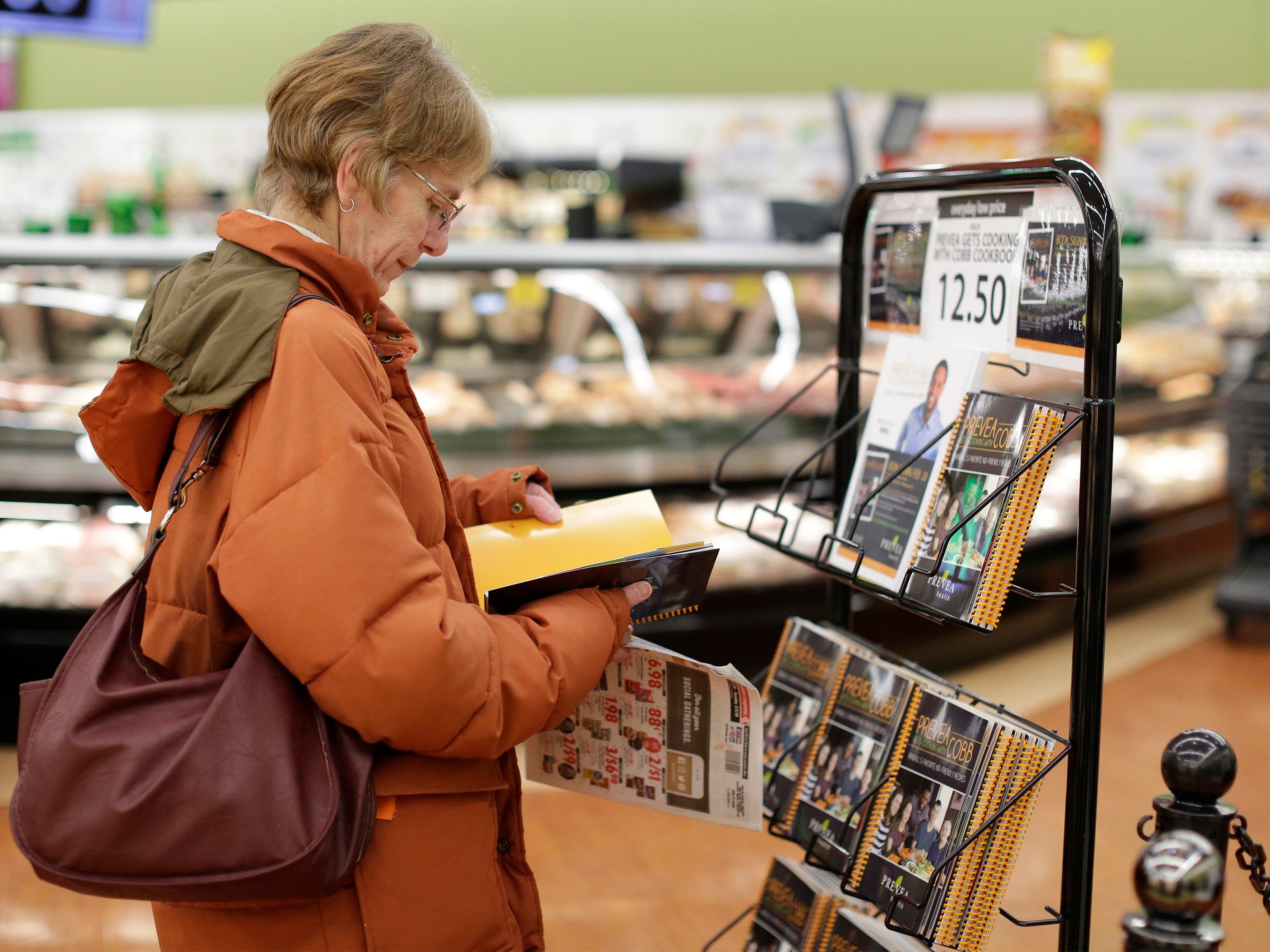 """Judy Bonnett of Parnell, Wis., looks over a copy of """"Prevea Gets Cooking with Cobb: Randall's Favorite Kid-Friendly Recipes"""", Thursday, February 28, 2019, in Sheboygan, Wis."""