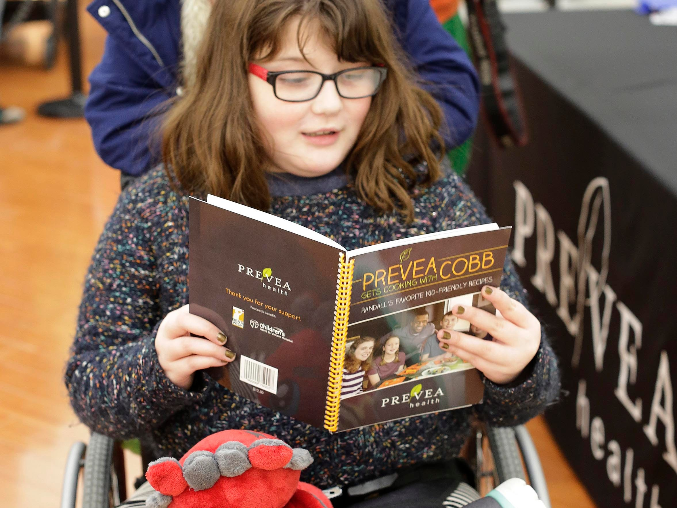 Lorelai Burke, 10, of Sheboygan, reads her the cookbook she had signed by Green Bay Packer Randall Cobb at Festival Foods, Thursday, February 28, 2019, in Sheboygan, Wis. Burke suffers from brittle bone disease.