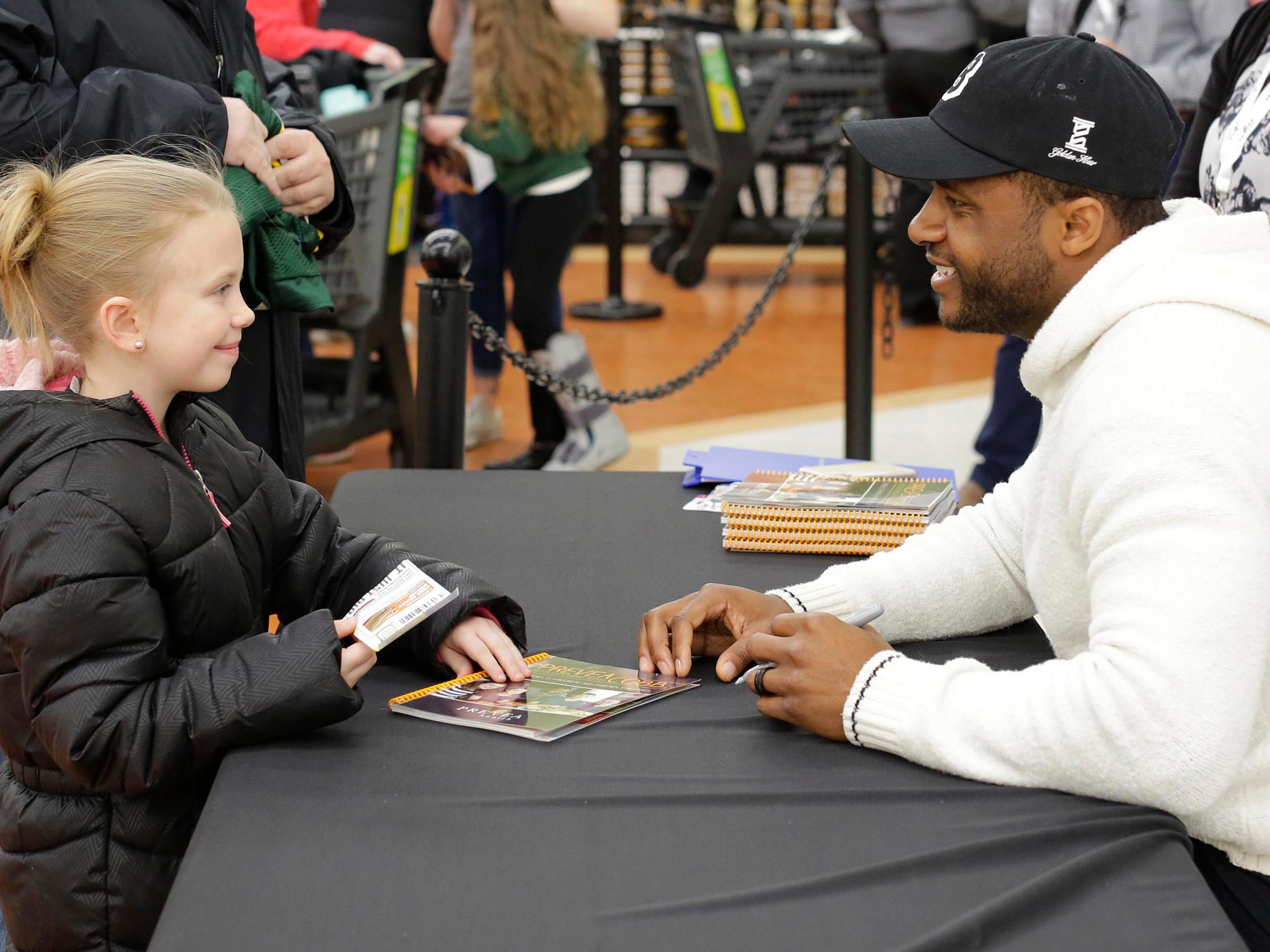 """Mackenzie Ratliff, 7, of Oostburg, Wis., smiles at Randall Cobb after he signed a cookbook called, """"Prevea Gets Cooking with Cobb: Randall's Favorite Kid-Friendly Recipes"""", Thursday, February 28, 2019, in Sheboygan, Wis."""