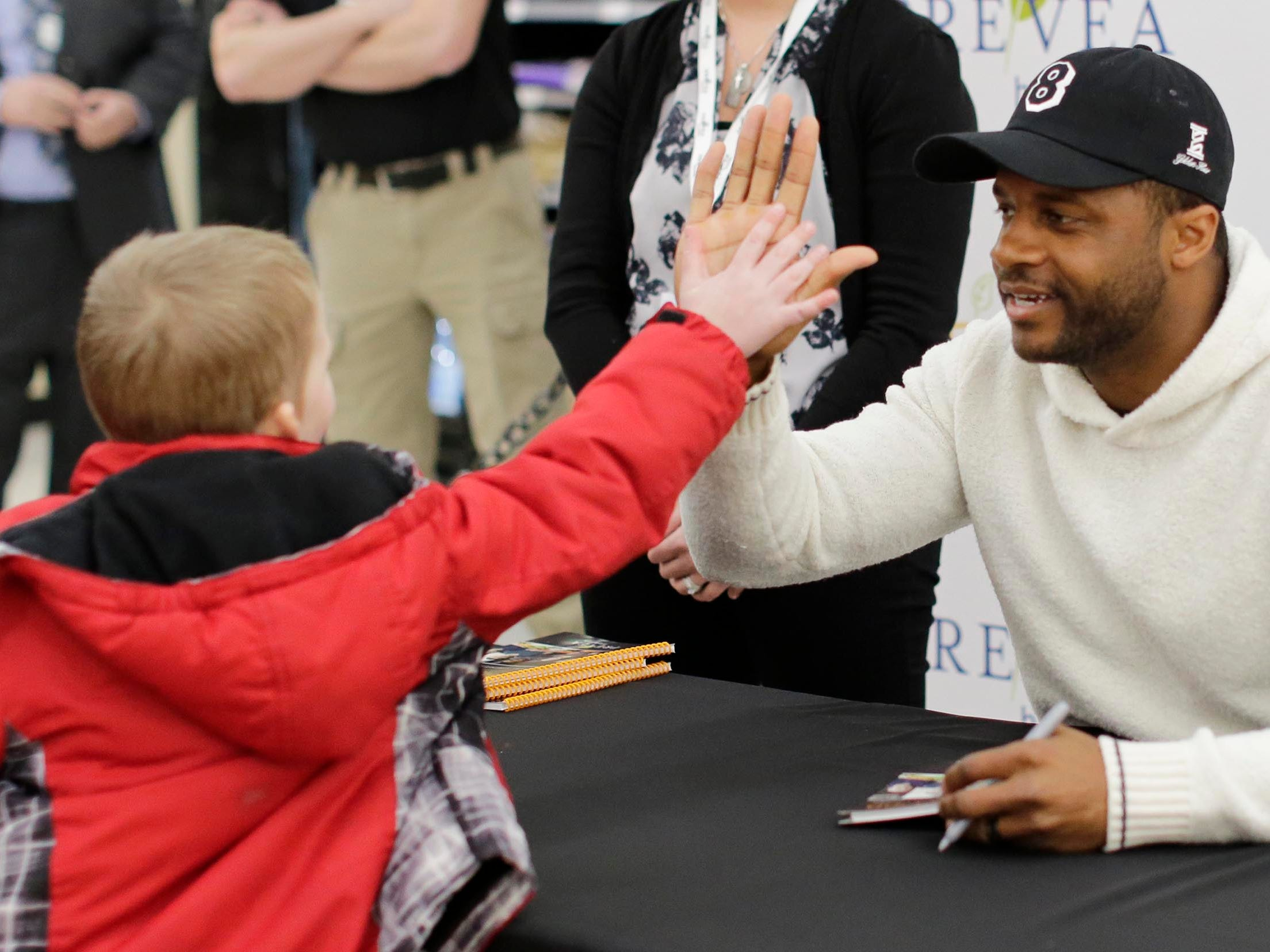 """Josiah Arentsen, 5, of Cedar Grove, gets a high five from Green Bay Packer Randall Cobb, Thursday, February 28, 2019, in Sheboygan, Wis. Cobb was at Festival Foods in Sheboygan to sign copies of """"Prevea Gets Cooking with Cobb: Randall's Favorite Kid-Friendly Recipes""""."""