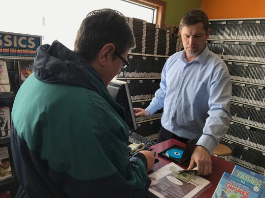 Dan Ahlers, owner of Video Plus, rings up a customer at his Dell Rapids video rental store. Ahlers plans to close Video Plus mid-March, with the last day of rentals set for Sunday.